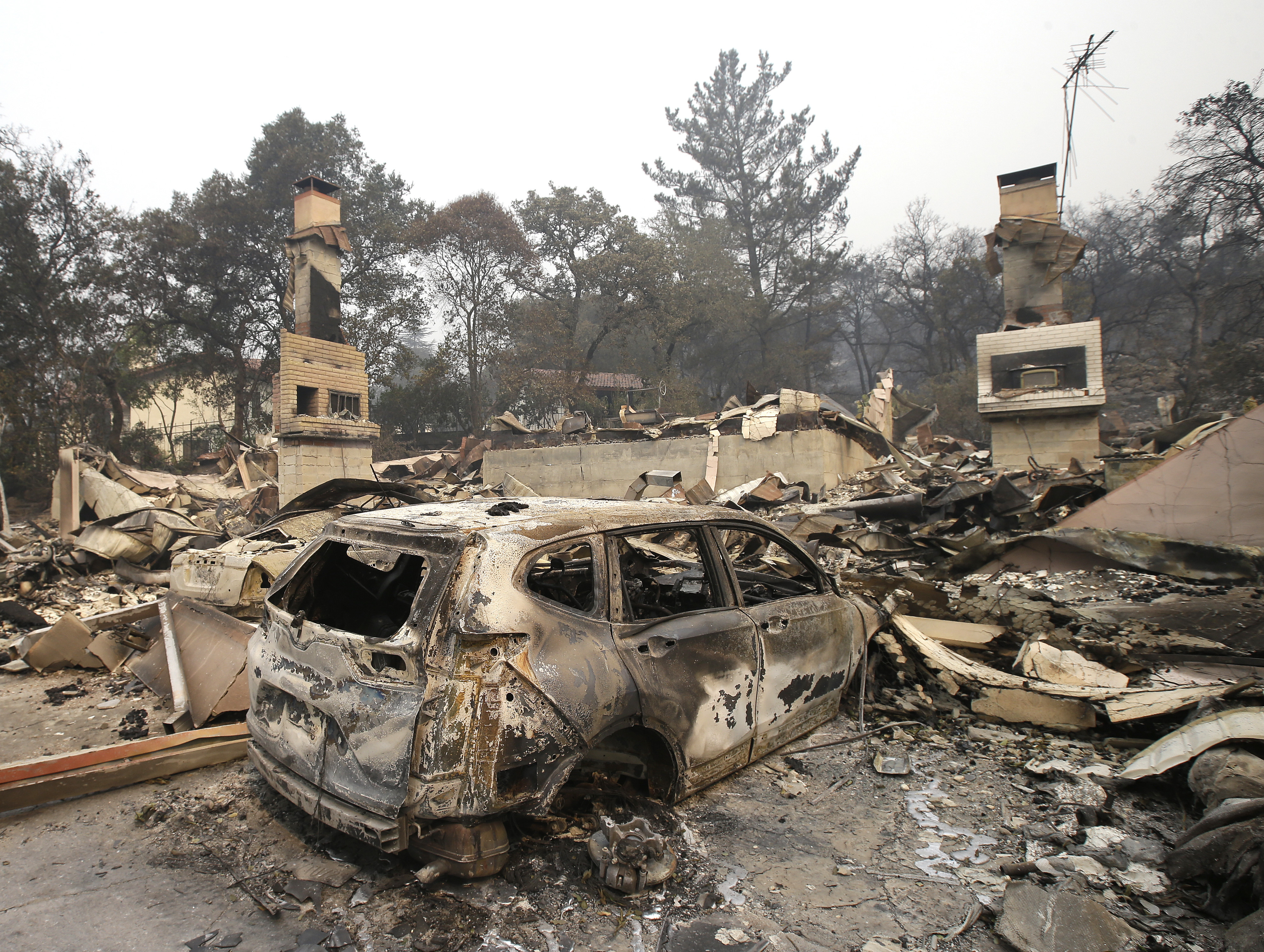 The burned remains of a car sit in the driveway of a home near the Silverado Country Club and Resort, Oct. 10, 2017, Napa, Calif.