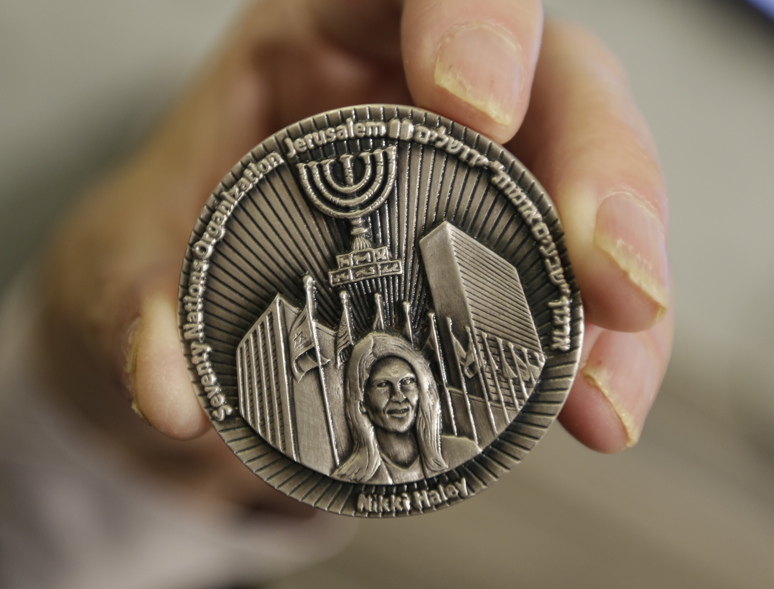 This March 13, 2019, photo shows a coin emblazoned with the face of Nikki Haley, President Donald Trump's former ambassador to the United Nations, to commemorate her defense of Israel in the United Nations, in Jerusalem.