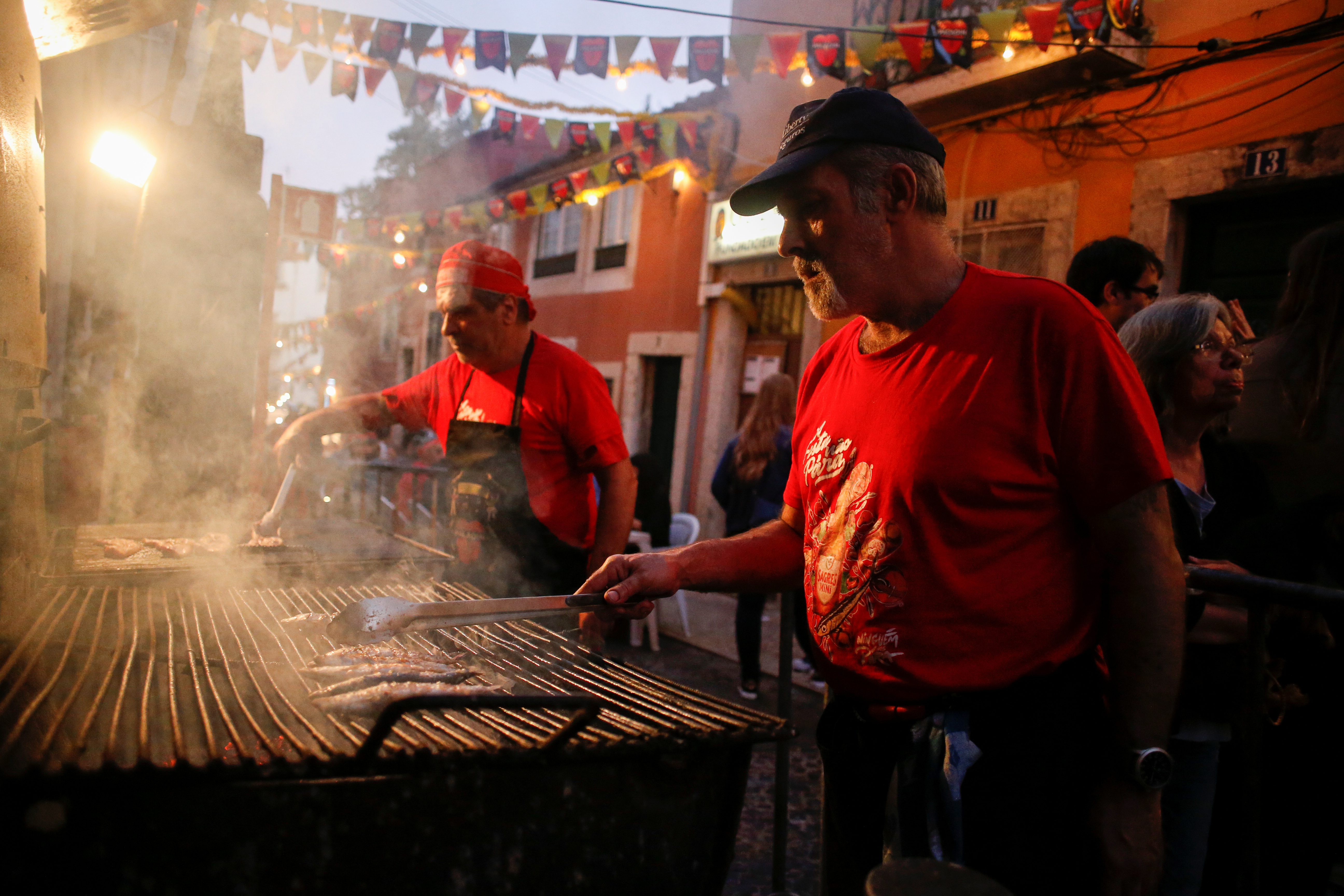 A man grills sardines in the Bica neighborhood in Lisbon, Portugal, June 14, 2018.