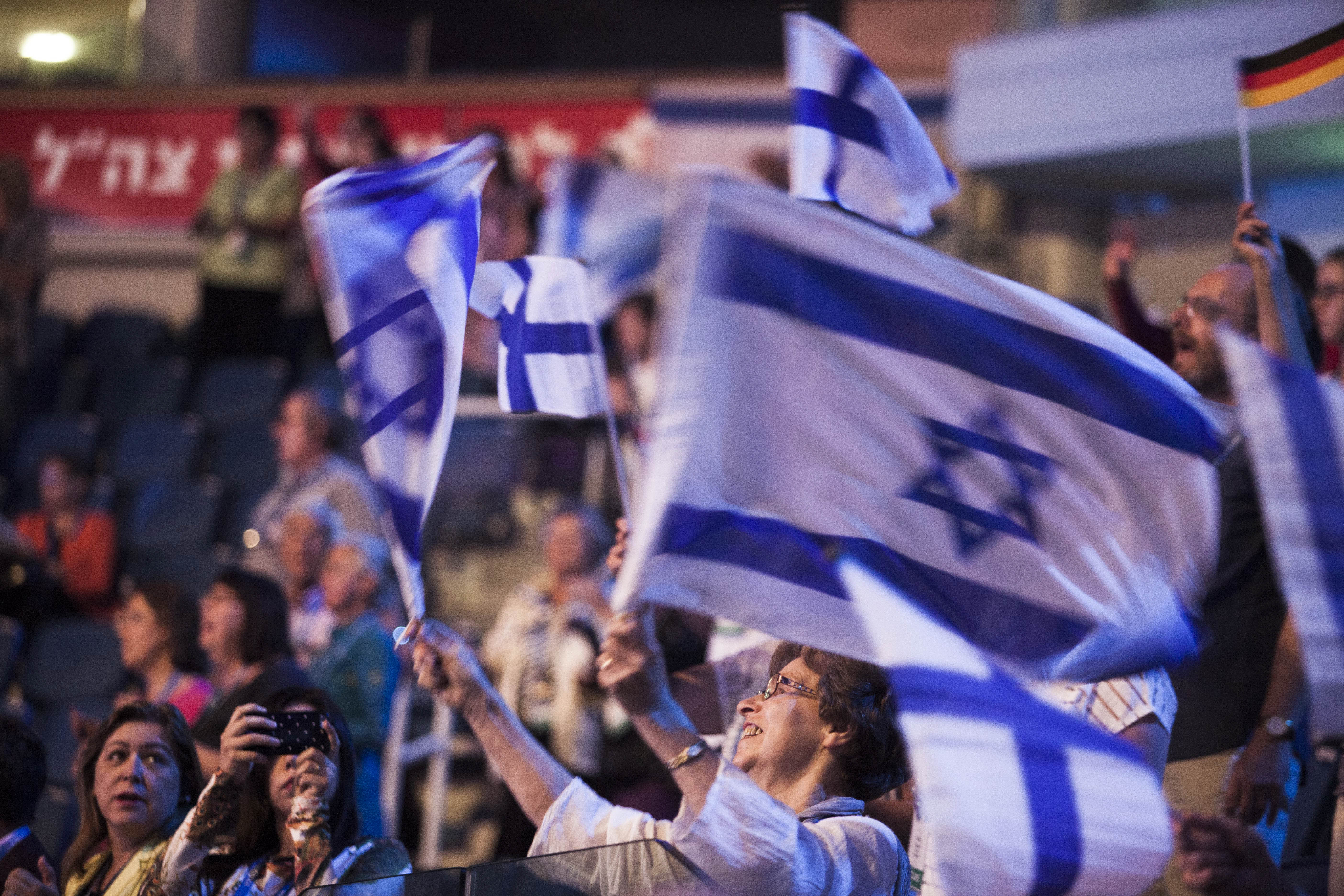 In this photo taken Sept. 29, 2015, an Evangelical Christian holds Israeli flags during a gathering in Jerusalem.