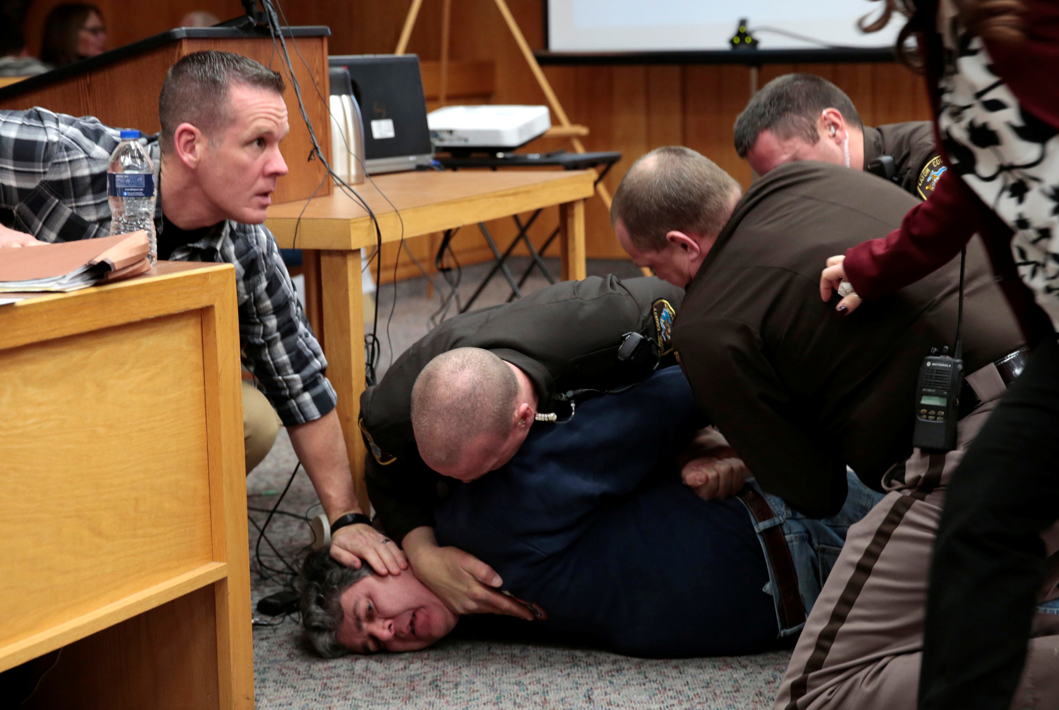 Eaton County sheriffs restrain Randall Margraves after he lunged at Larry Nassar, a former team USA Gymnastics doctor who pleaded guilty in November 2017 to sexual assault charges, during victim statements of his sentencing in the Eaton County Circui...