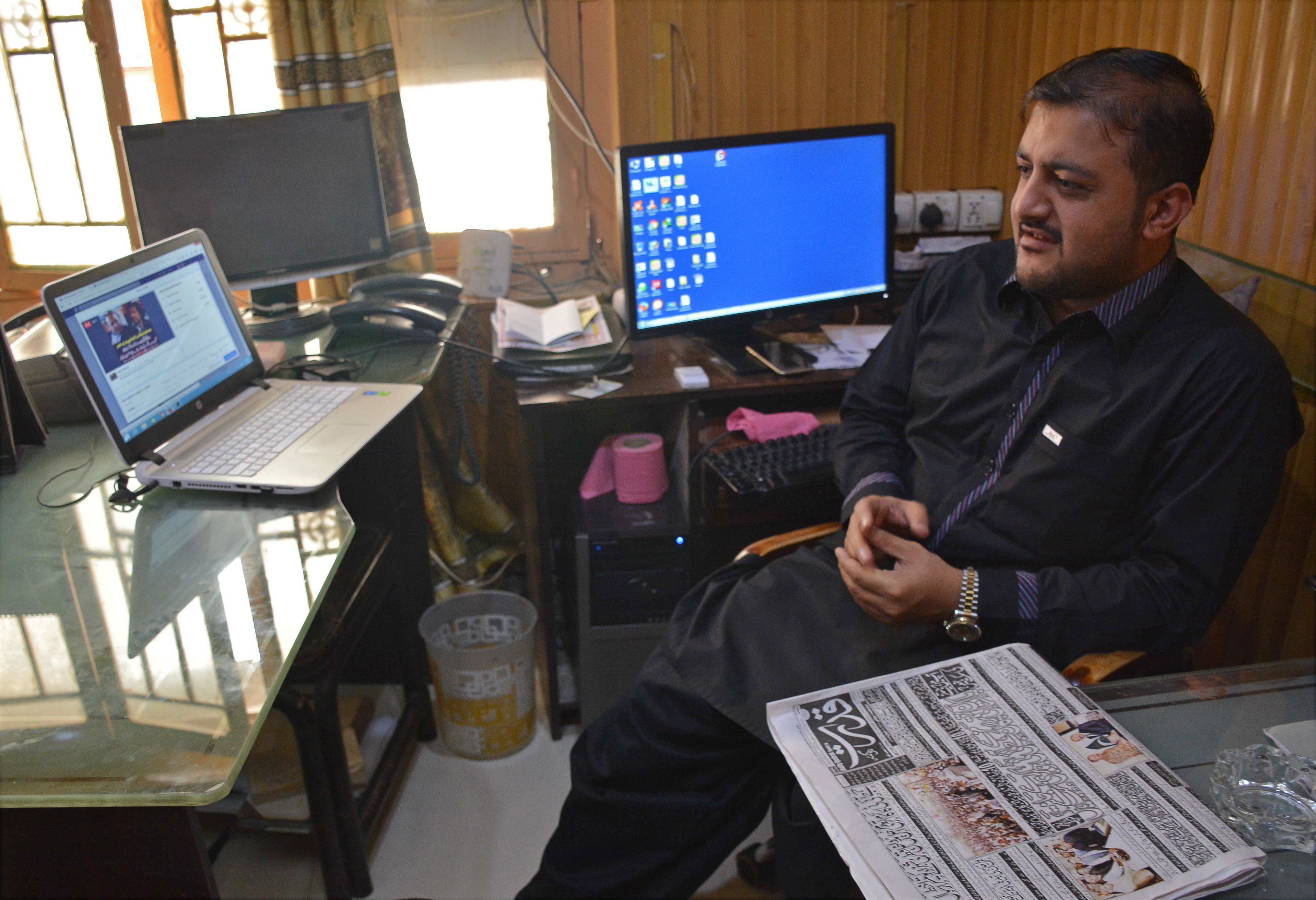 FILE - Journalist Zafar Achakzai, who was held for sharing content criticizing security forces on social media, sits in his office after being released from jail, in Quetta, Pakistan, July 9, 2017.