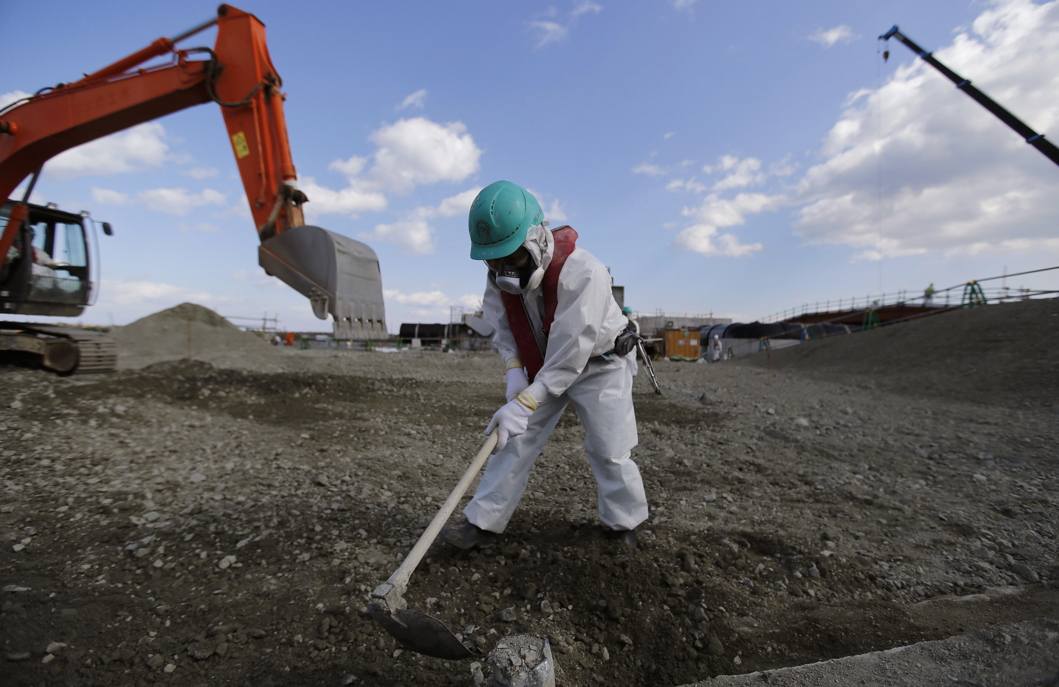 A worker, wearing a protective suit and a mask, levels ground at the tsunami-crippled Fukushima Dai-ichi nuclear power plant, operated by Tokyo Electric Power Co. (TEPCO), in Okuma, Fukushima Prefecture, northeastern Japan, Feb. 10, 2016.