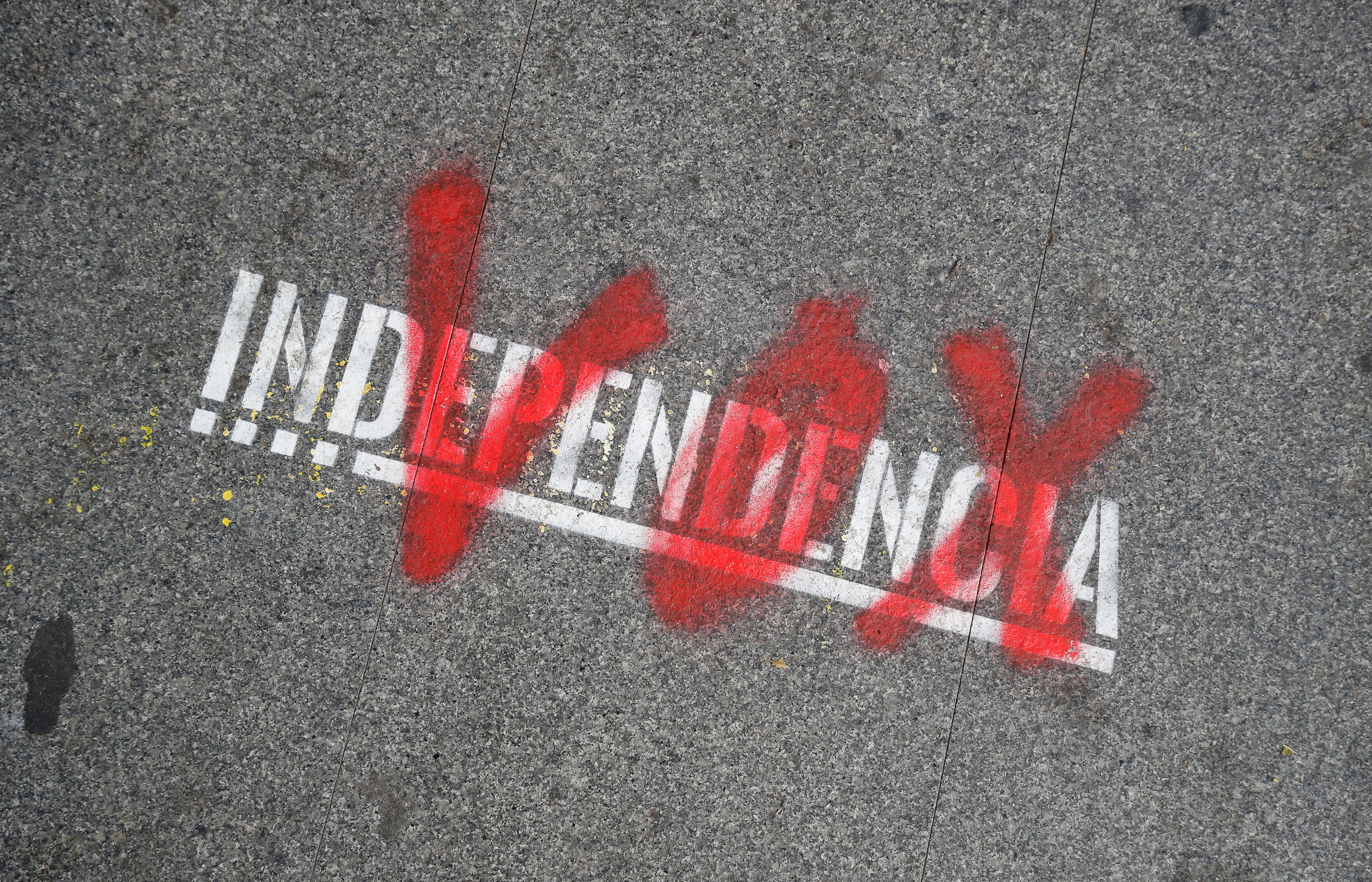 "FILE - The name of the Spanish right-wing party Vox is sprayed over the graffiti stencil reading ""Independence"" on sidewalk in Barcelona, Spain, Dec. 12, 2018."