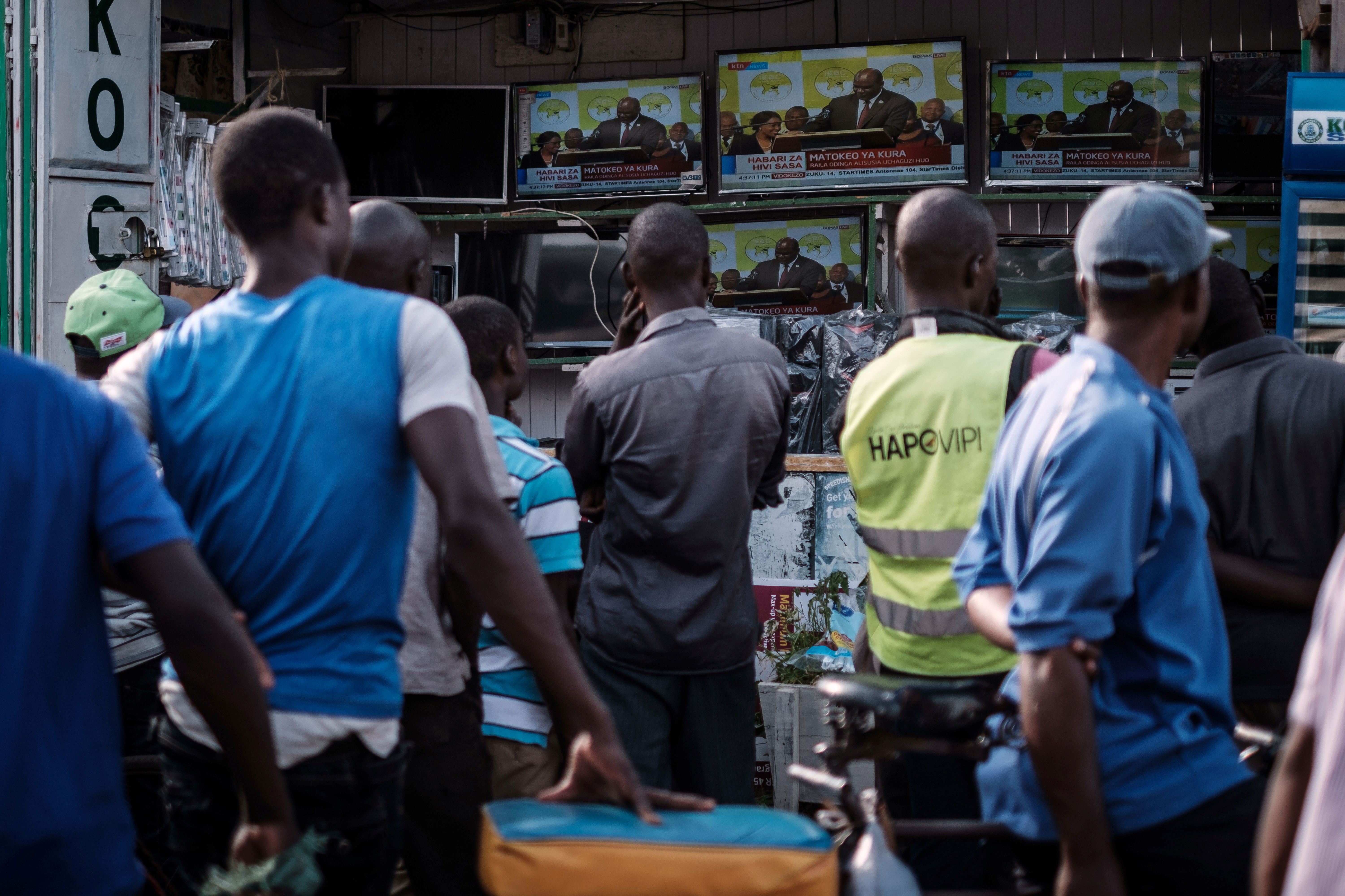 People watch a live broadcast of the announcement of the re-election results by Kenya's Independent Electoral and Boundaries Commission (IEBC) chairman, Wafula Chebukat, on TV at a local electrical shop in Kisumu, Oct. 30, 2017.