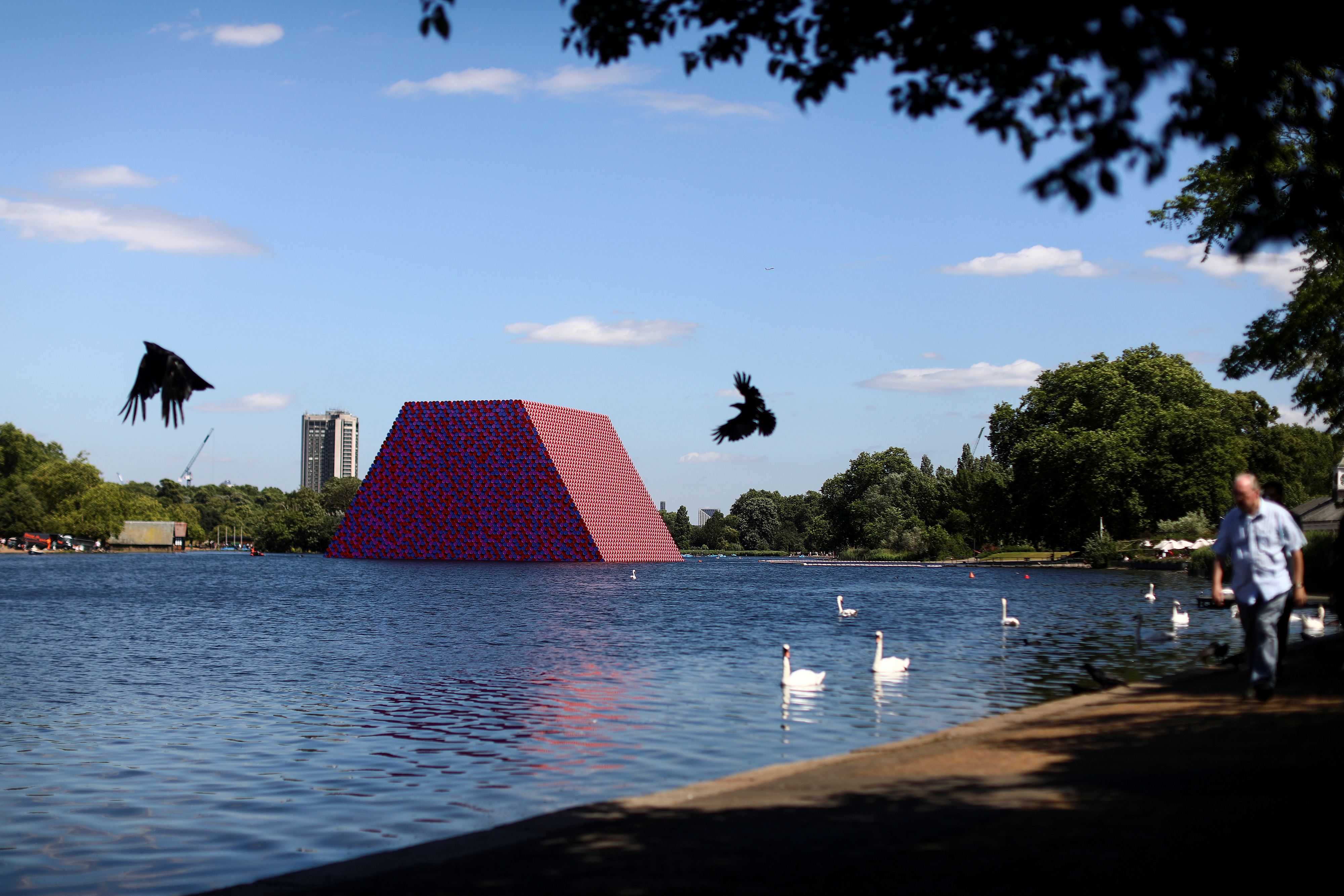 People walk past 'The London Mastaba' by artist Christo as it sits on the Serpentine in Hyde Park, London, Britain, June 18, 2018.