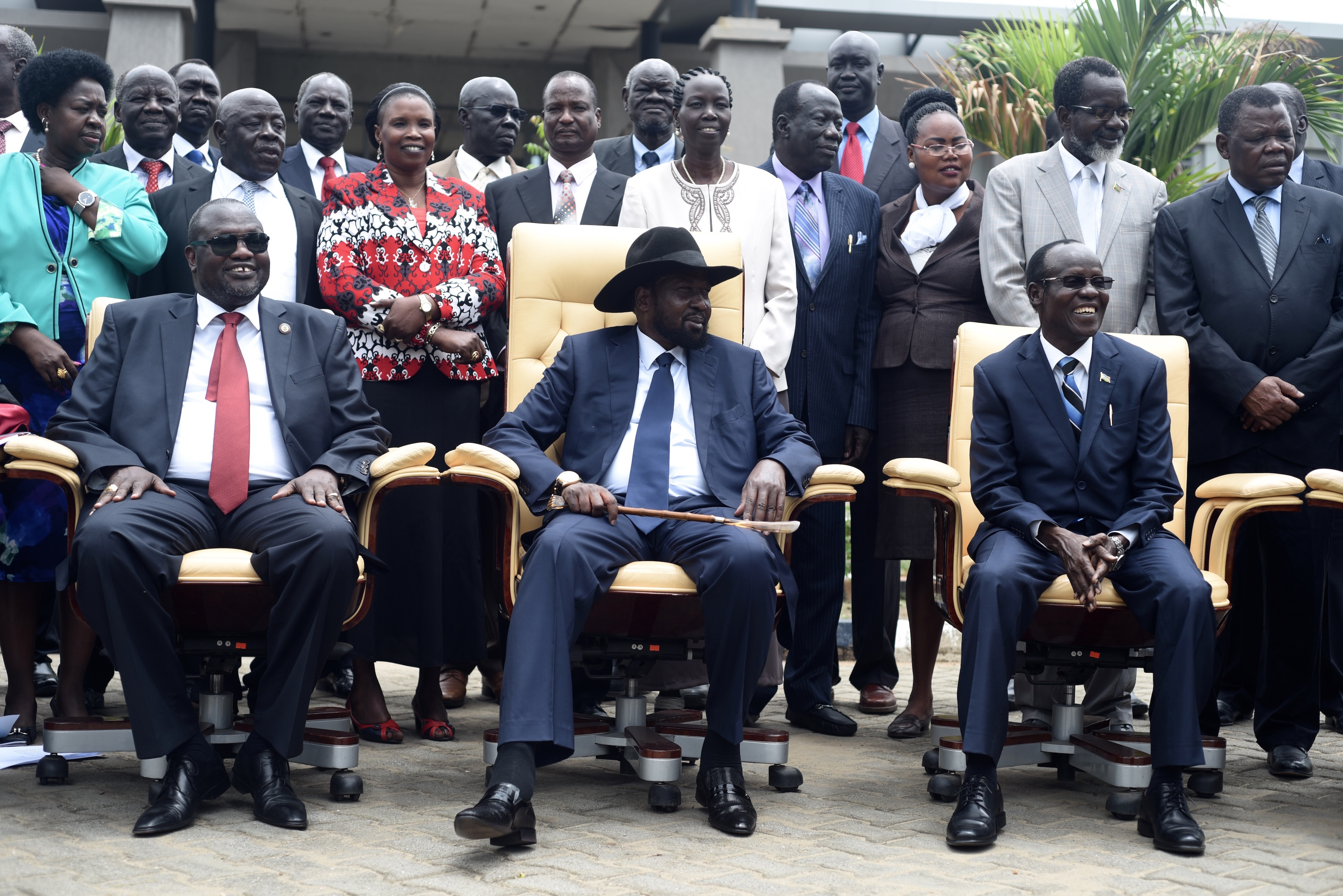 South Sudan's President Salva Kiir, center, laughs with First Vice President Riek Machar, left, and Vice President James Wani Igga, right, while cabinet members stand behind them, after the first meeting of a new transitional government of national u...