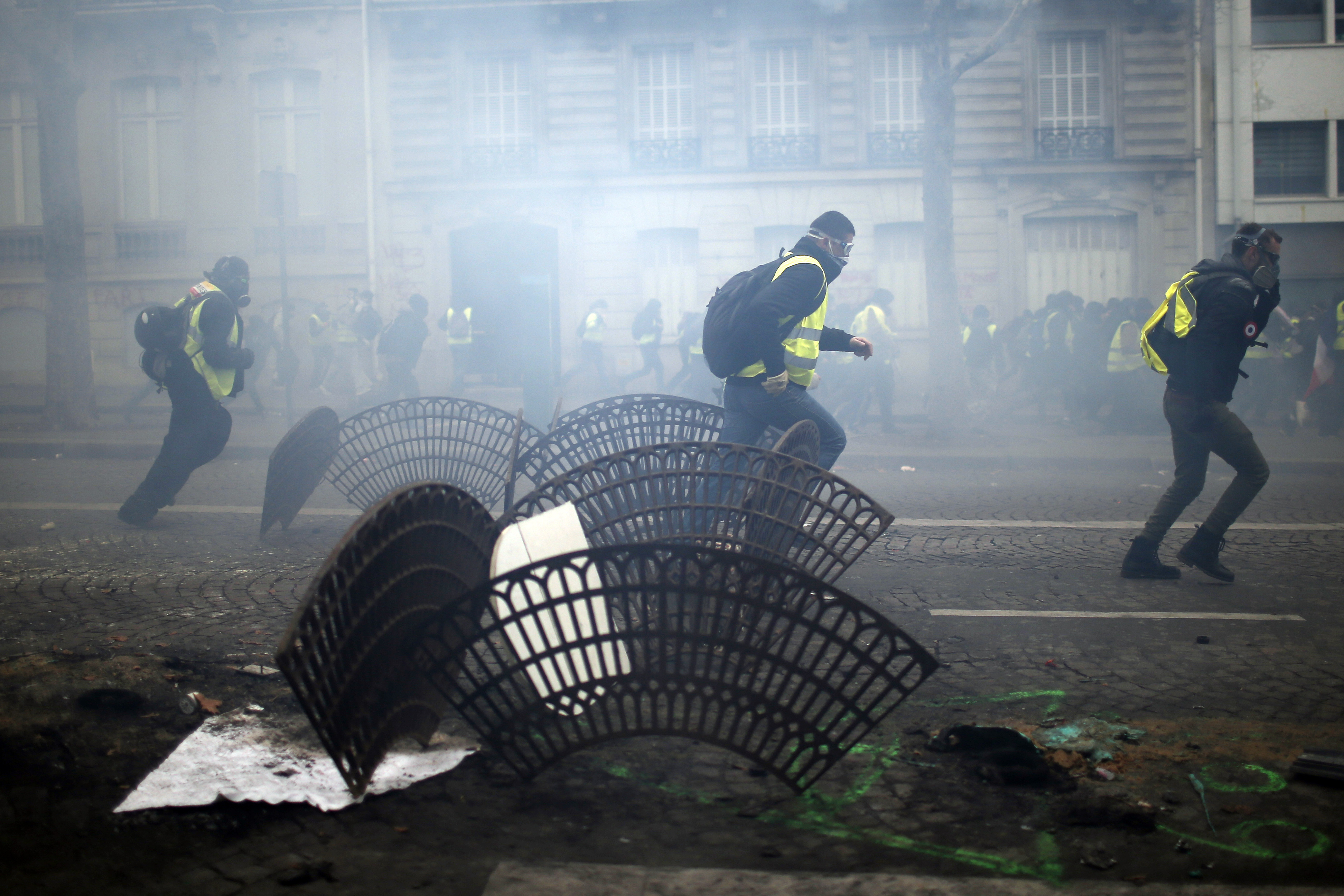 Demonstrators run away during clashes Saturday, Dec. 8, 2018 in Paris. Crowds of yellow-vested protesters angry at President Emmanuel Macron and France's high taxes tried to converge on the presidential palace Saturday, some scuffling with police fir