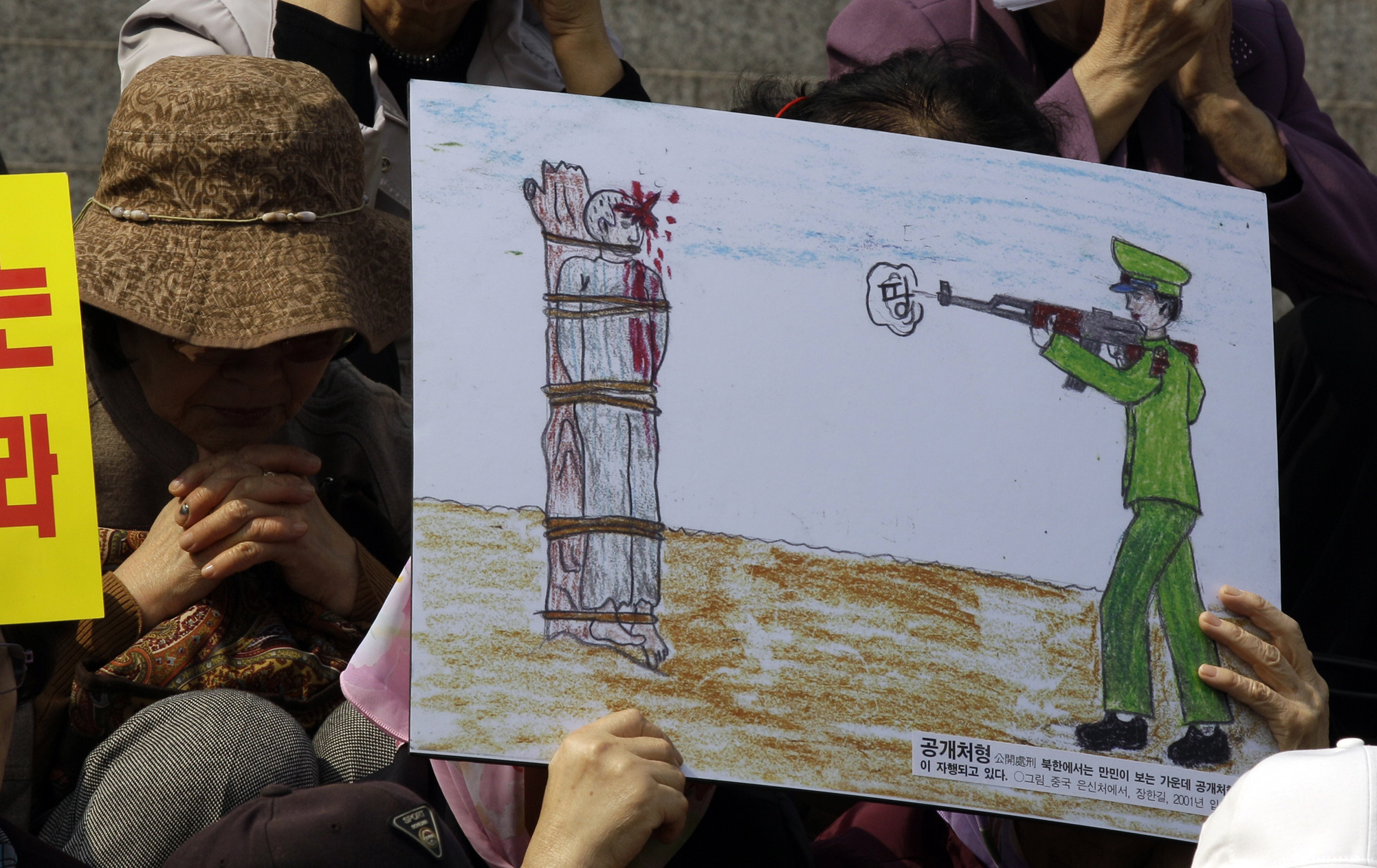 FILE - A North Korean defector reacts next to a drawing depicting a public execution of a North Korean soldier during a human rights rally in Seoul, South Korea, April 14, 2011.