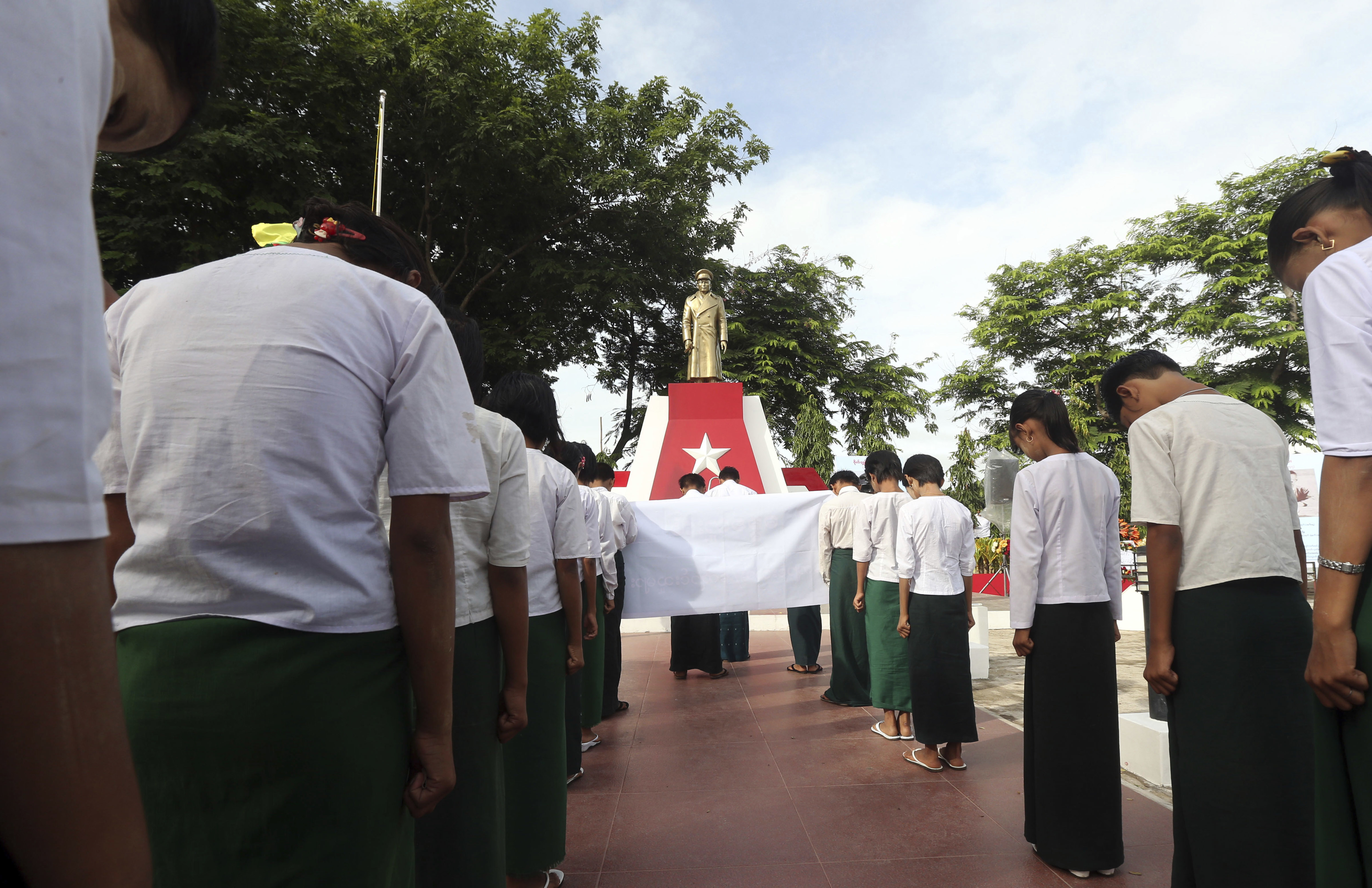 FILE - Students bow before a statue of Myanmar national hero Gen. Aung San during a ceremony in Naypyitaw, Myanmar, July 19, 2017.