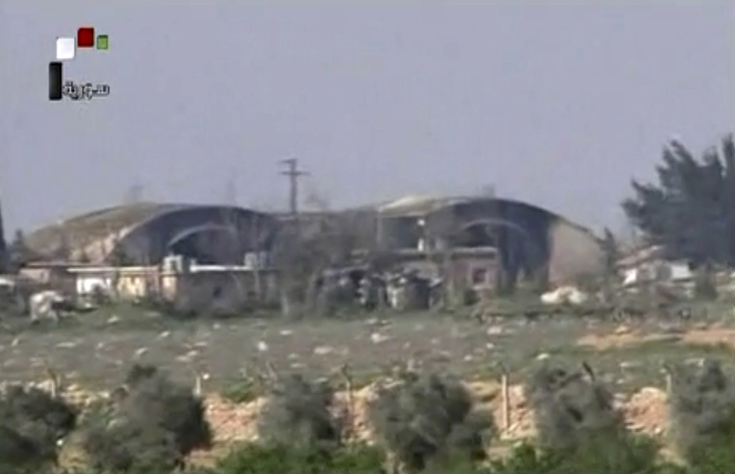 FILE - This frame grab from video provided April, 7, 2017, by official Syrian TV shows the burned and damaged hangars hit by U.S. Tomahawk missiles at the Shayrat air base southeast of Homs, Syria.