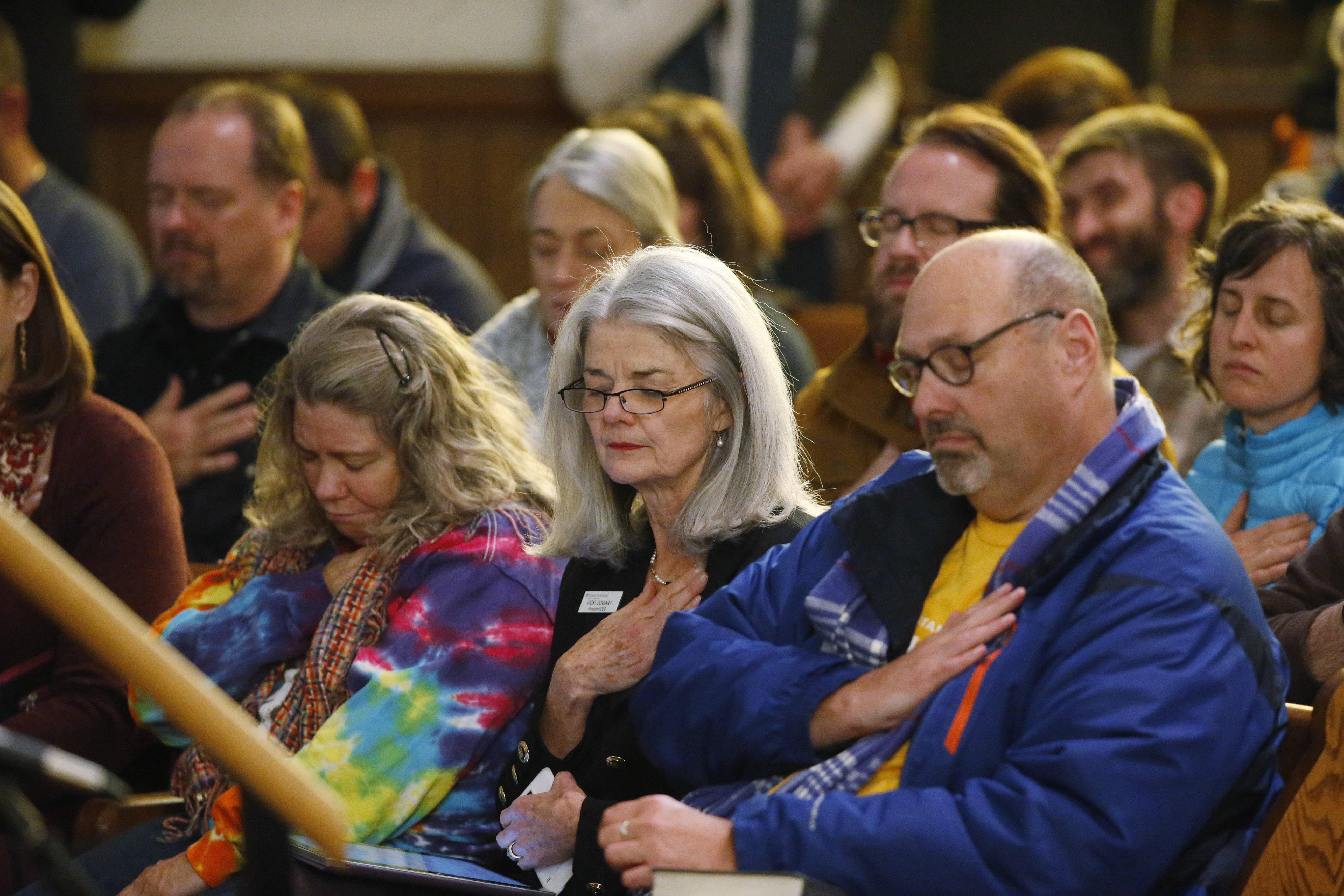 Vicki Cowart, center, executive director of Planned Parenthood of the Rocky Mountains, joins others in putting their hands on their hearts at All Souls Unitarian Universalist Church in Colorado Springs, Colo., during a vigil for victims of Friday's s...