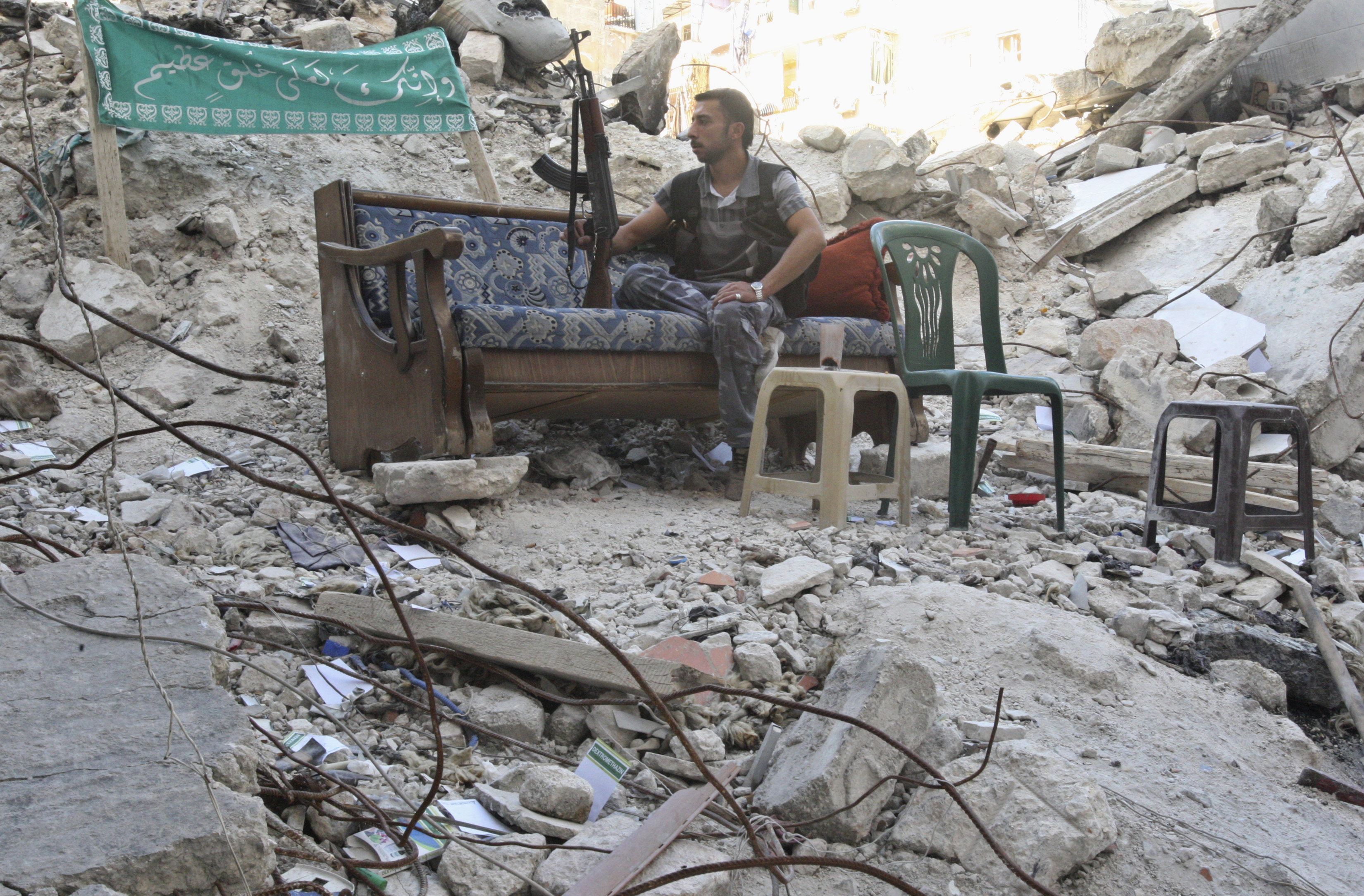A Free Syrian Army fighter sits on a sofa along a street in Aleppo's Salaheddine neighbourhood July 30, 2013. Picture taken July 30, 2013. REUTERS/ Ammar Abdullah (SYRIA - Tags: CONFLICT) - RTX125S0
