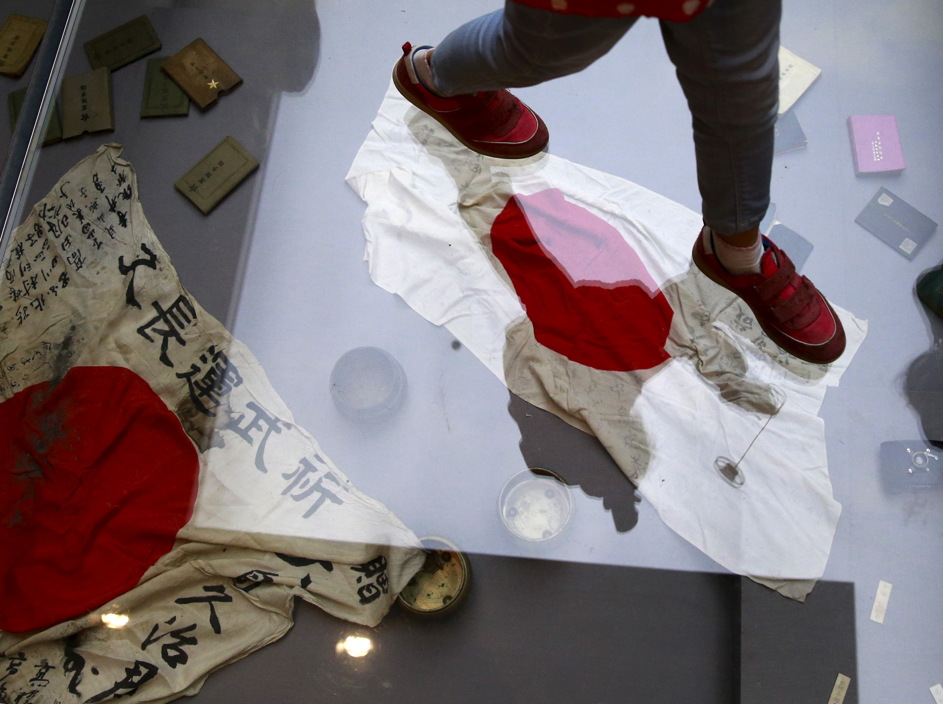 A visitor walks on a glass flooring above Japanese military flags seized by the Chinese People's Liberation Army (PLA) during World War II, at the Museum of the War of Chinese People's Resistance Against Japanese Aggression, in Beijing, China, Sept. ...