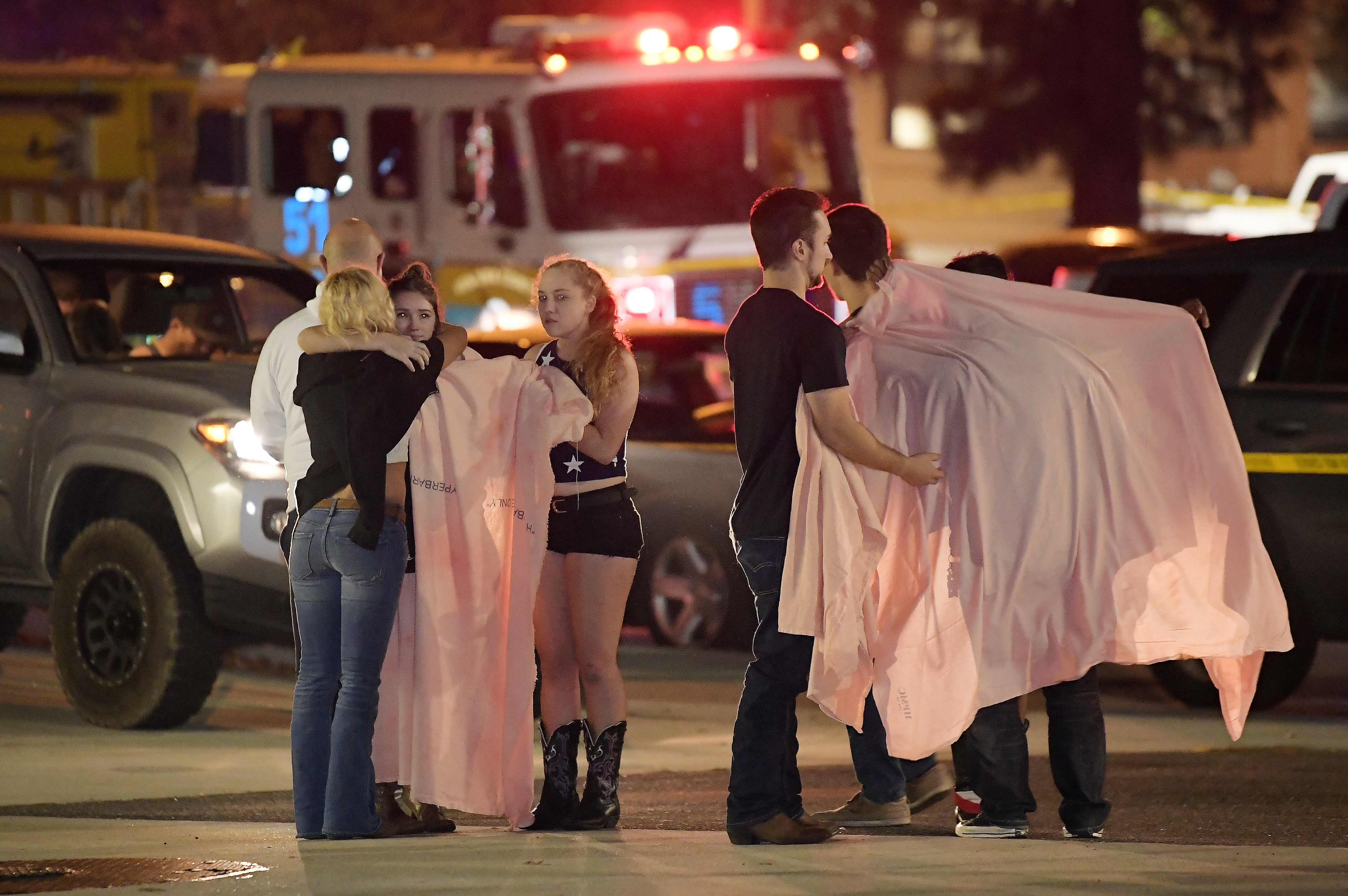 People comfort each other as they stand near the scene in Thousand Oaks, Calif., where a gunman opened fire Wednesday inside a country dance bar crowded with hundreds of people Nov. 8, 2018.