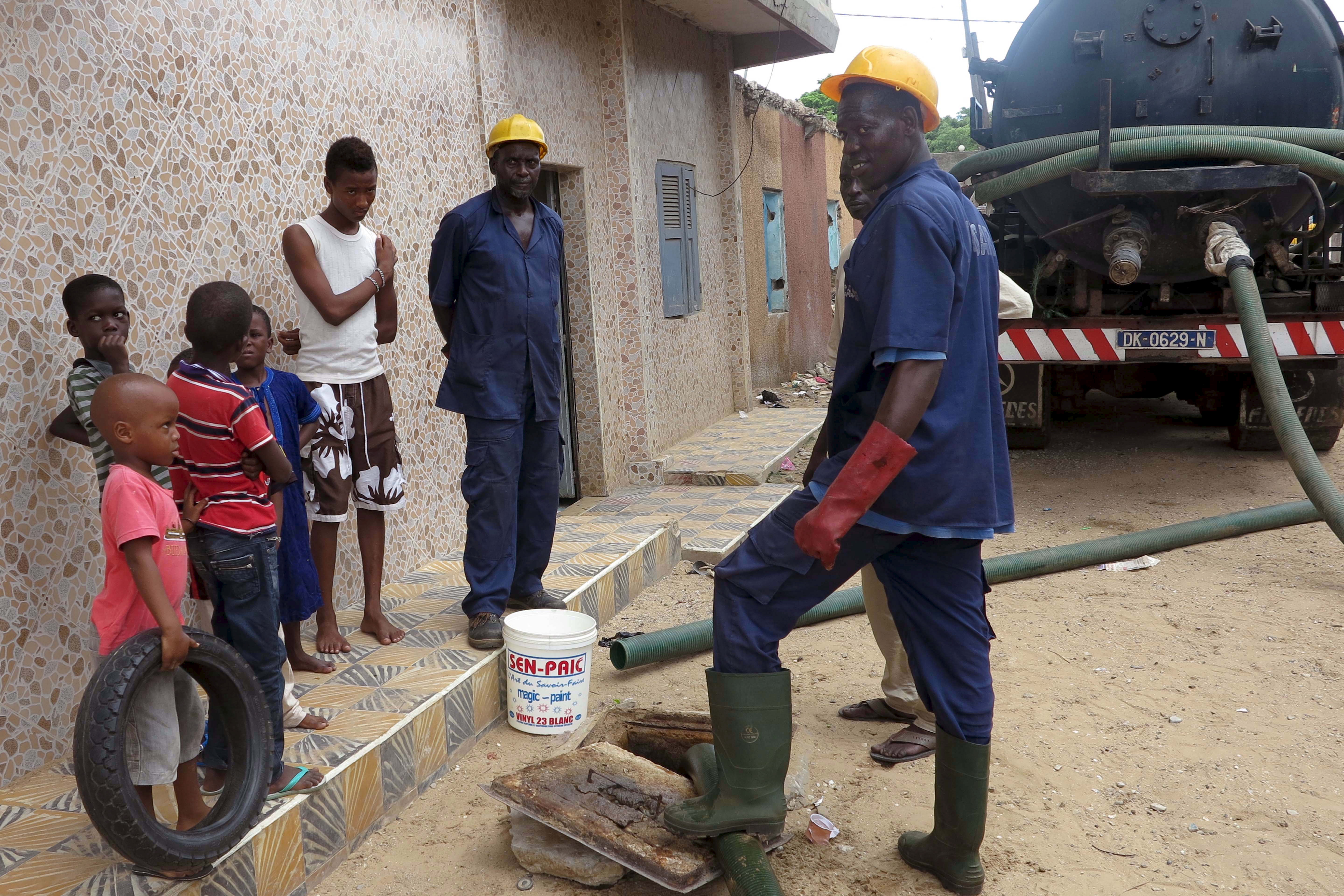 FILE - Sanitation workers removes septic waste from a house in Guediawaye, Senegal, Aug. 19, 2015. Government and charitable organizations are installing new toilets that turn waste into compost or break down matter with worms in bid to lower health ...