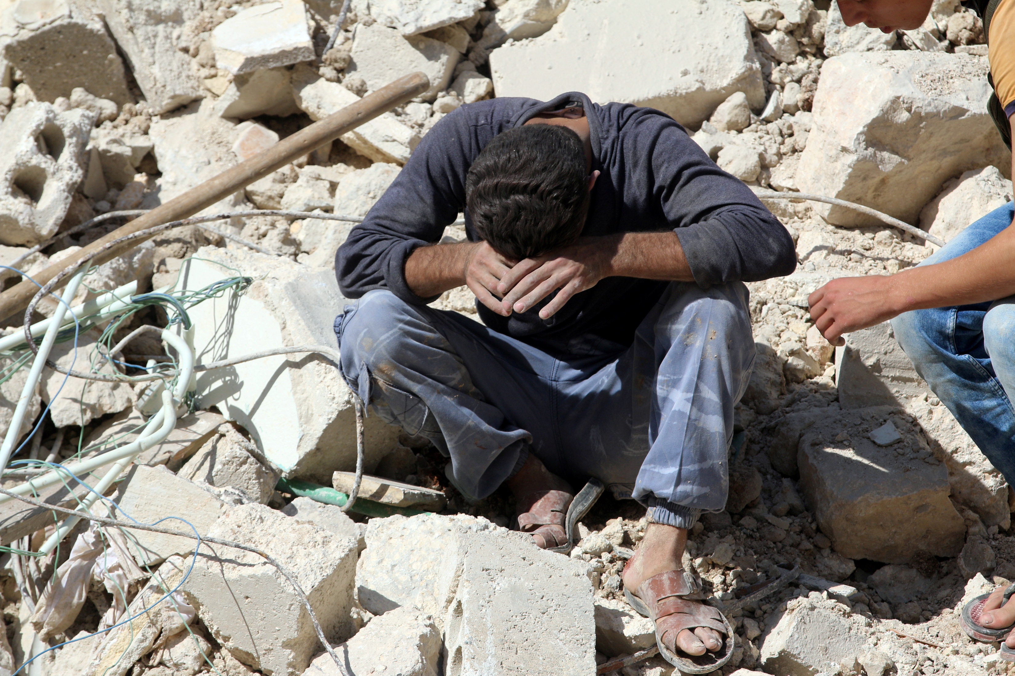 A man reacts on the rubble of damaged buildings after losing relatives to an airstrike in the besieged rebel-held al-Qaterji neighborhood of Aleppo, Syria, Oct. 11, 2016.