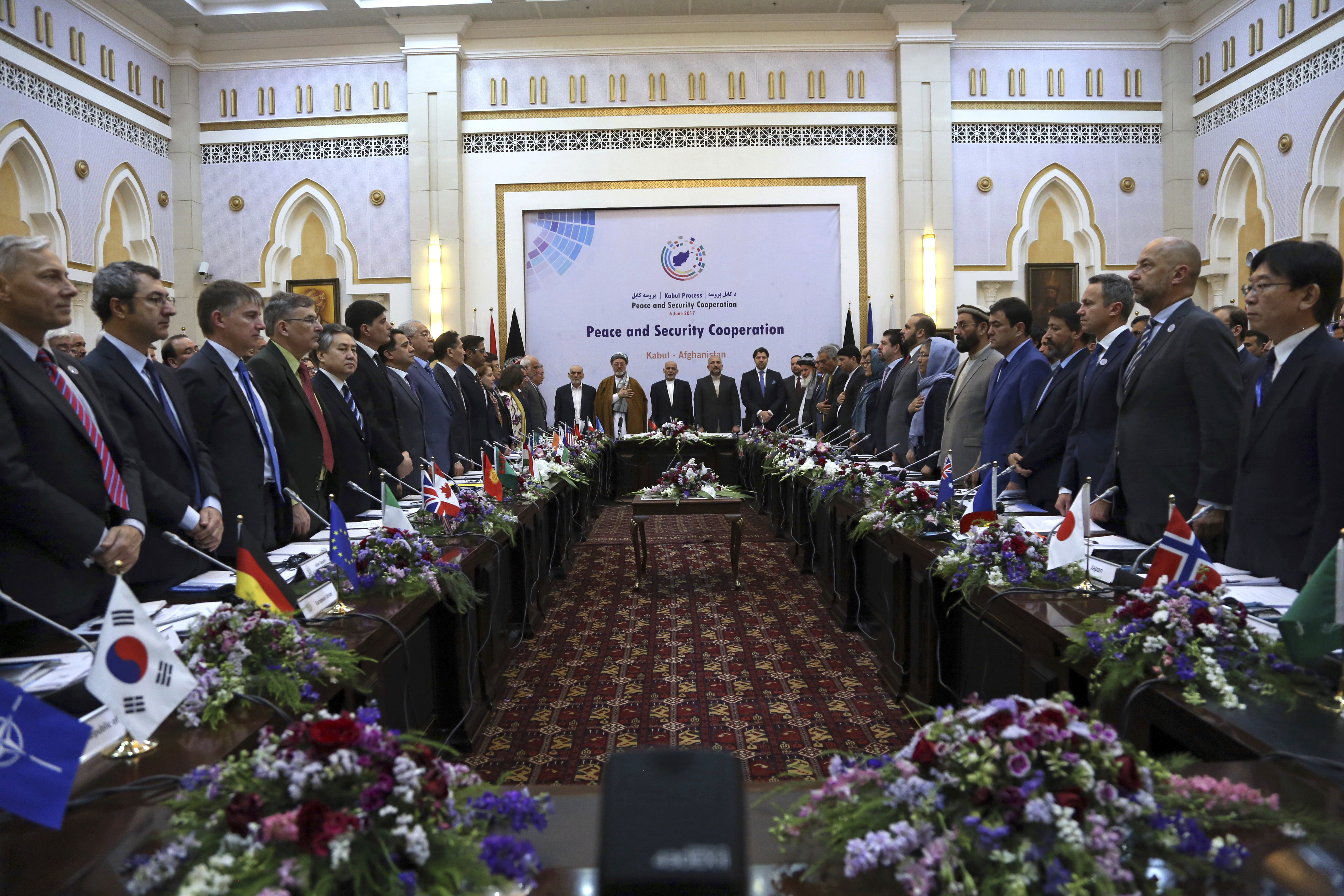 FILE - Afghan President Ashraf Ghani (C) and delegates stand for the national anthem during the Kabul Process conference, at the Presidential Palace in Kabul, Afghanistan, June 6, 2017.