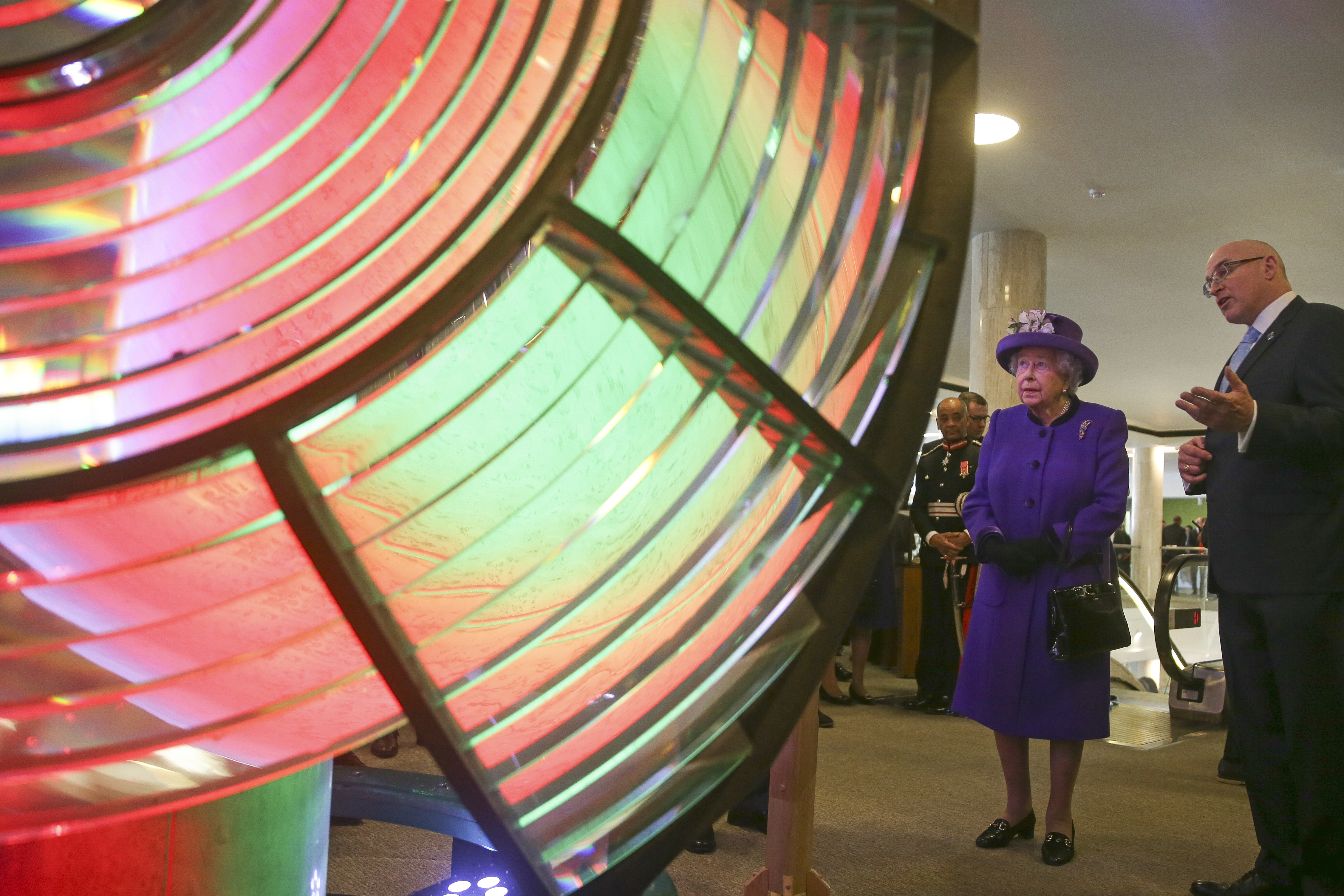 FILE - Britain's Queen Elizabeth II looks at an optic from the decommissioned Orfordness Lighthouse, built by Chance Brothers of Smethwick and installed in Suffolk in 1913, during a visit to the International Maritime Organization in London, March 6,...