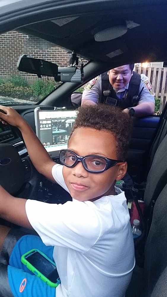 A boy gets a look inside a police car with Sergeant John Kim watching during National Night Out in Fairfax Country, Virginia, Aug. 2, 2016. (D. Block/VOA)
