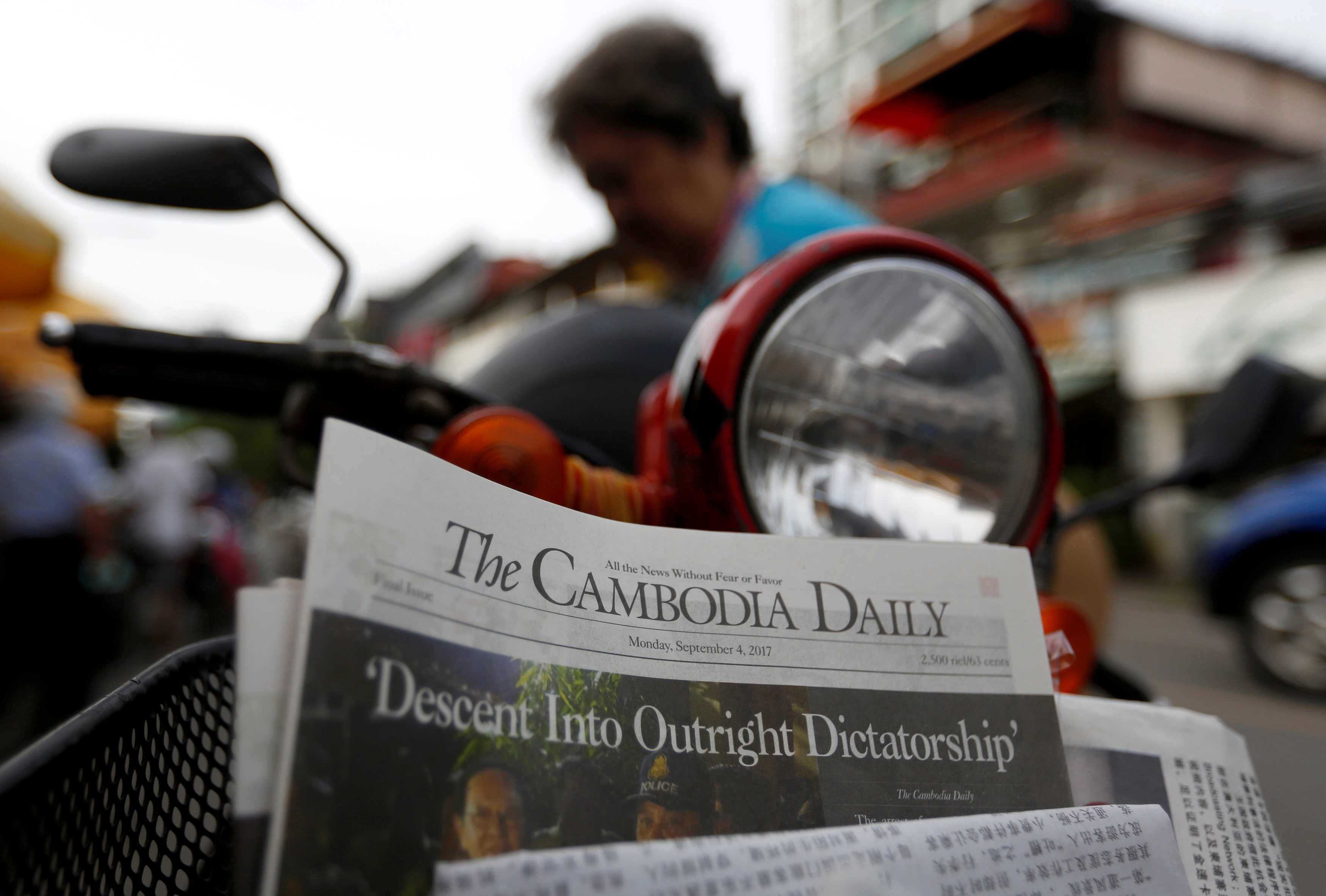 FILE - A woman buys the final issue of The Cambodia Daily newspaper at a store along a street in Phnom Penh, Cambodia, Sept. 4, 2017.