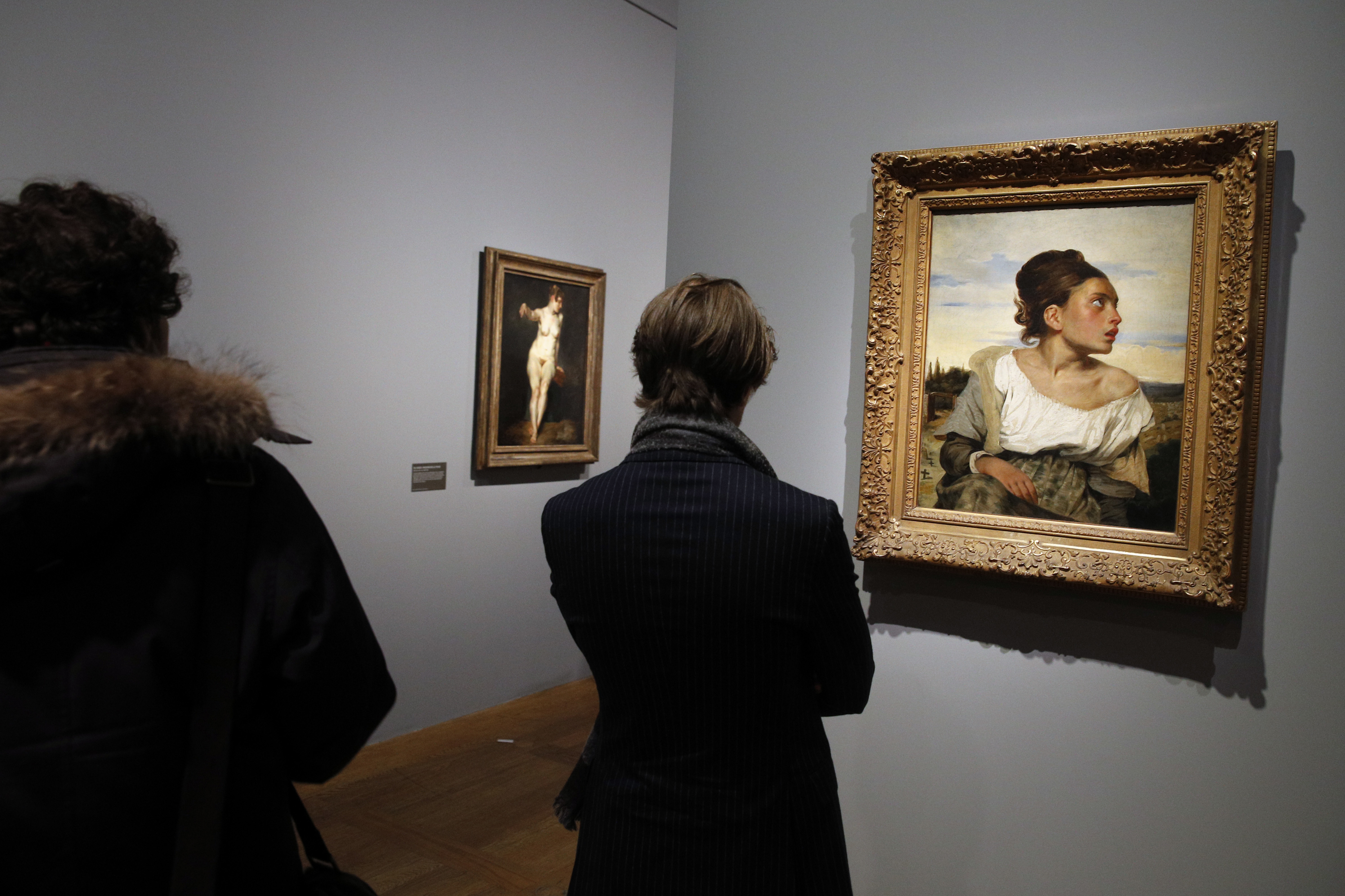 """Visitors look at """"Jeune orpheline au cimetiere"""" (""""Orphan Girl at the Cemetery"""") by Eugene Delacroix at the Louvre, in Paris, March 27, 2018."""