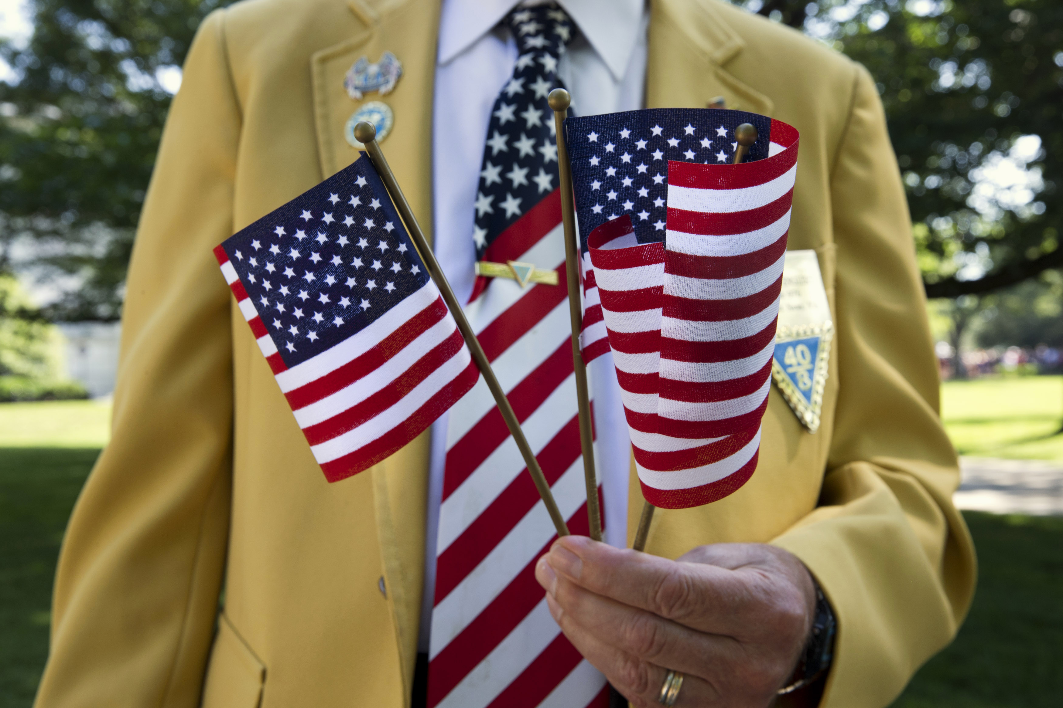 Navy veteran William Englert passes out U.S. flags to the crowd attending Memorial Day ceremonies at Arlington National Cemetery in Arlington, Va., Monday May 25, 2015.  (AP Photo/Jacquelyn Martin)