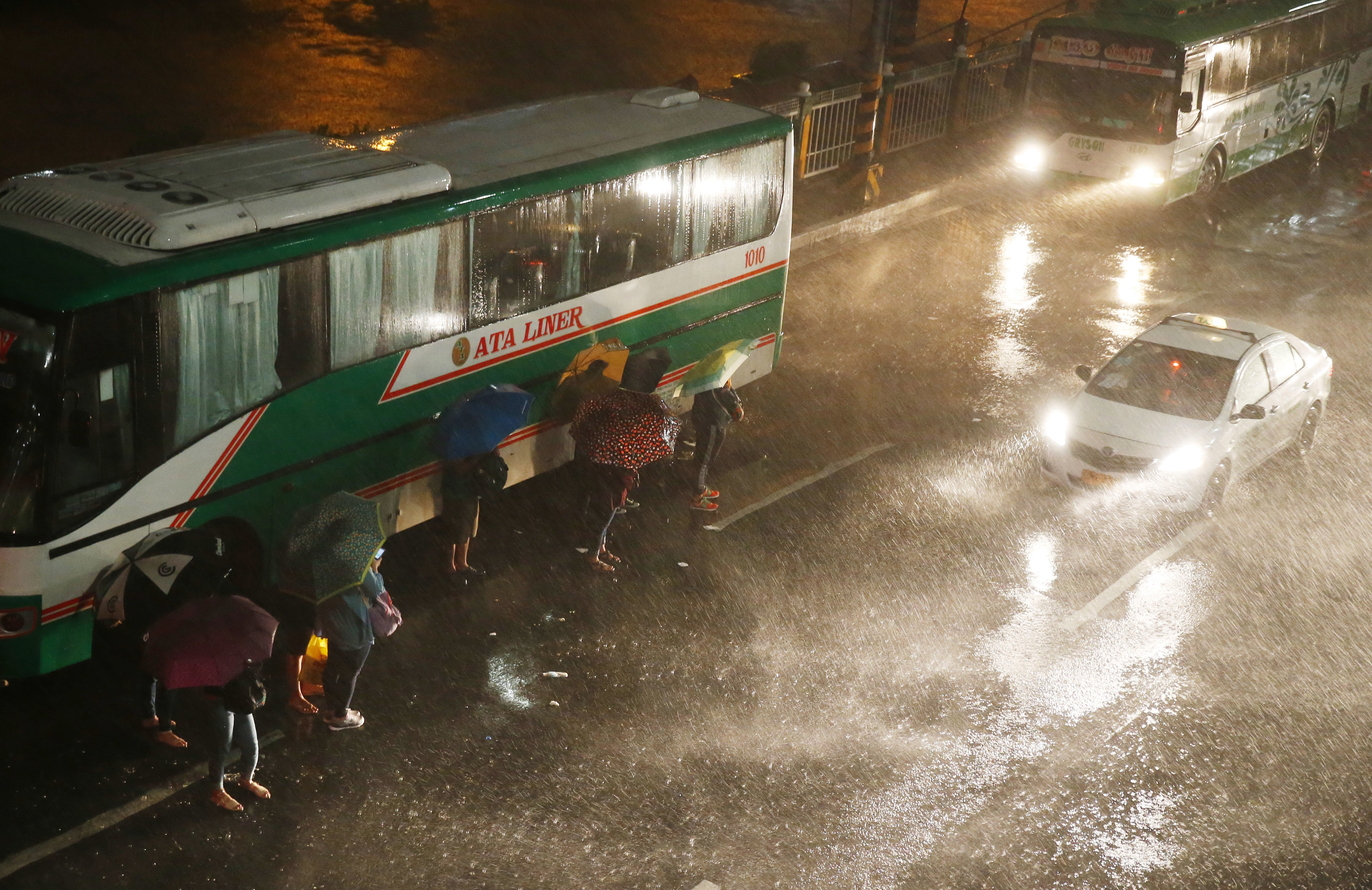 Commuters brave the rain and strong winds brought about by Typhoon Mangkhut, which barreled into northeastern Philippines before dawn, Sept. 15, 2018, in Manila, Philippines. Typhoon Mangkhut, the strongest typhoon to hit the country this year, slamm...