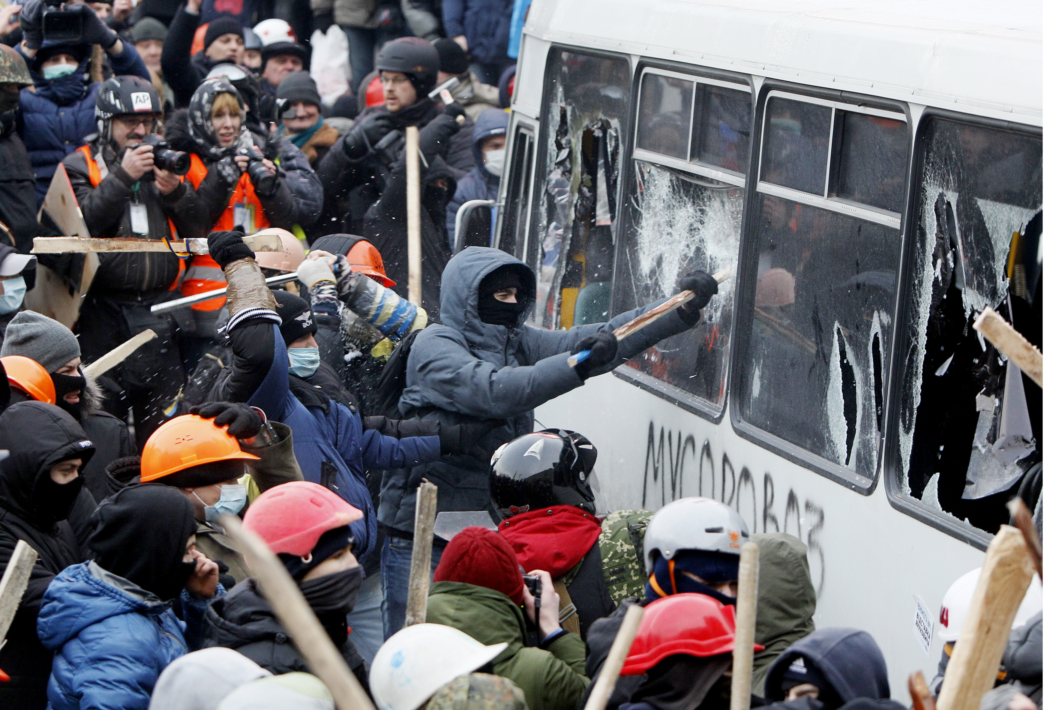 Pro-European protesters attack a police van during a rally near government administration buildings in Kiev January 19, 2014. Up to 100,000 Ukrainians massed in the capital Kiev on Sunday in defiance of sweeping new laws aimed at stamping out anti-go