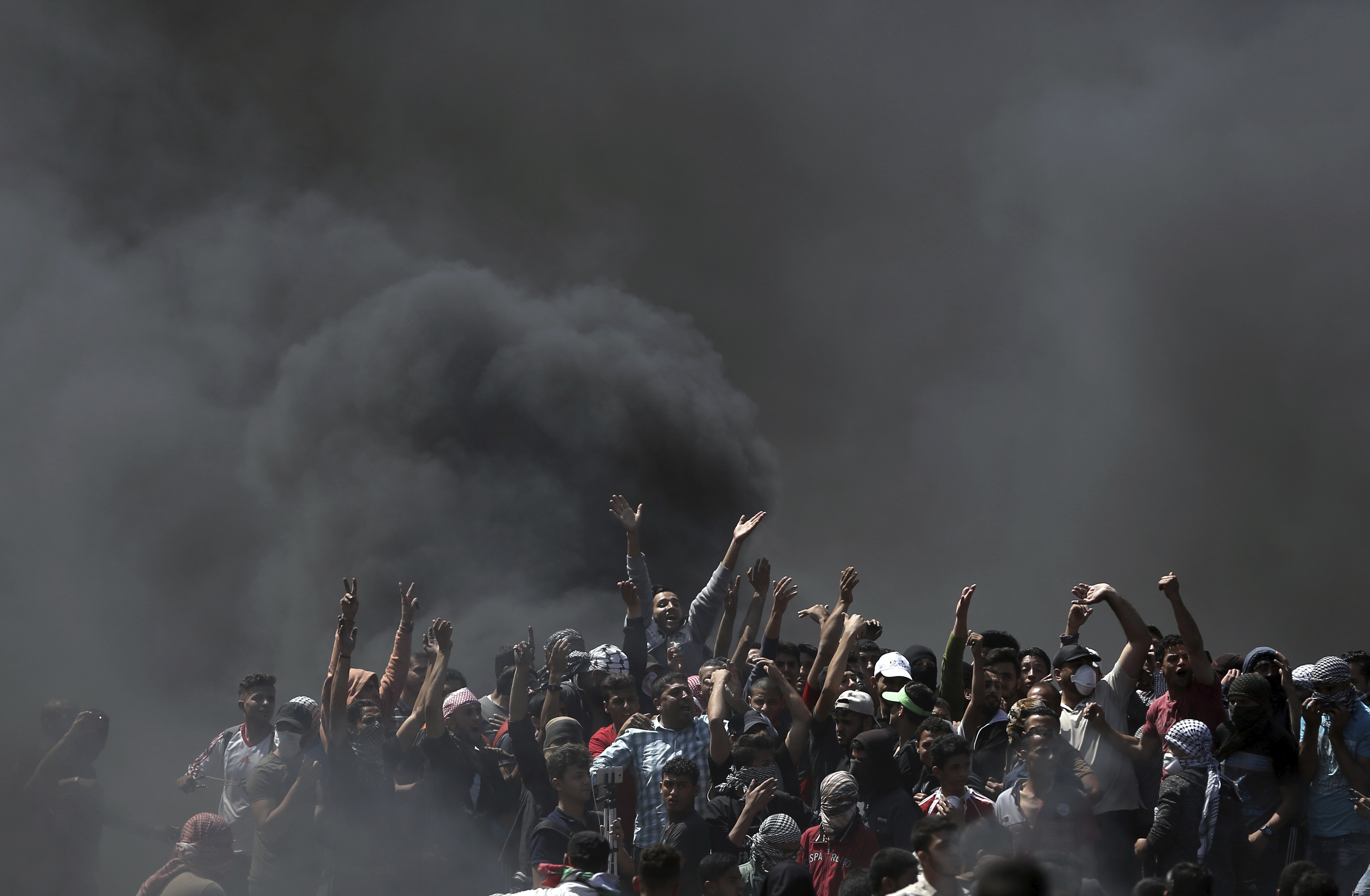 FILE- Palestinian protesters chant slogans as they burn tires during a protest on the Gaza Strip's border with Israel, May 14, 2018.