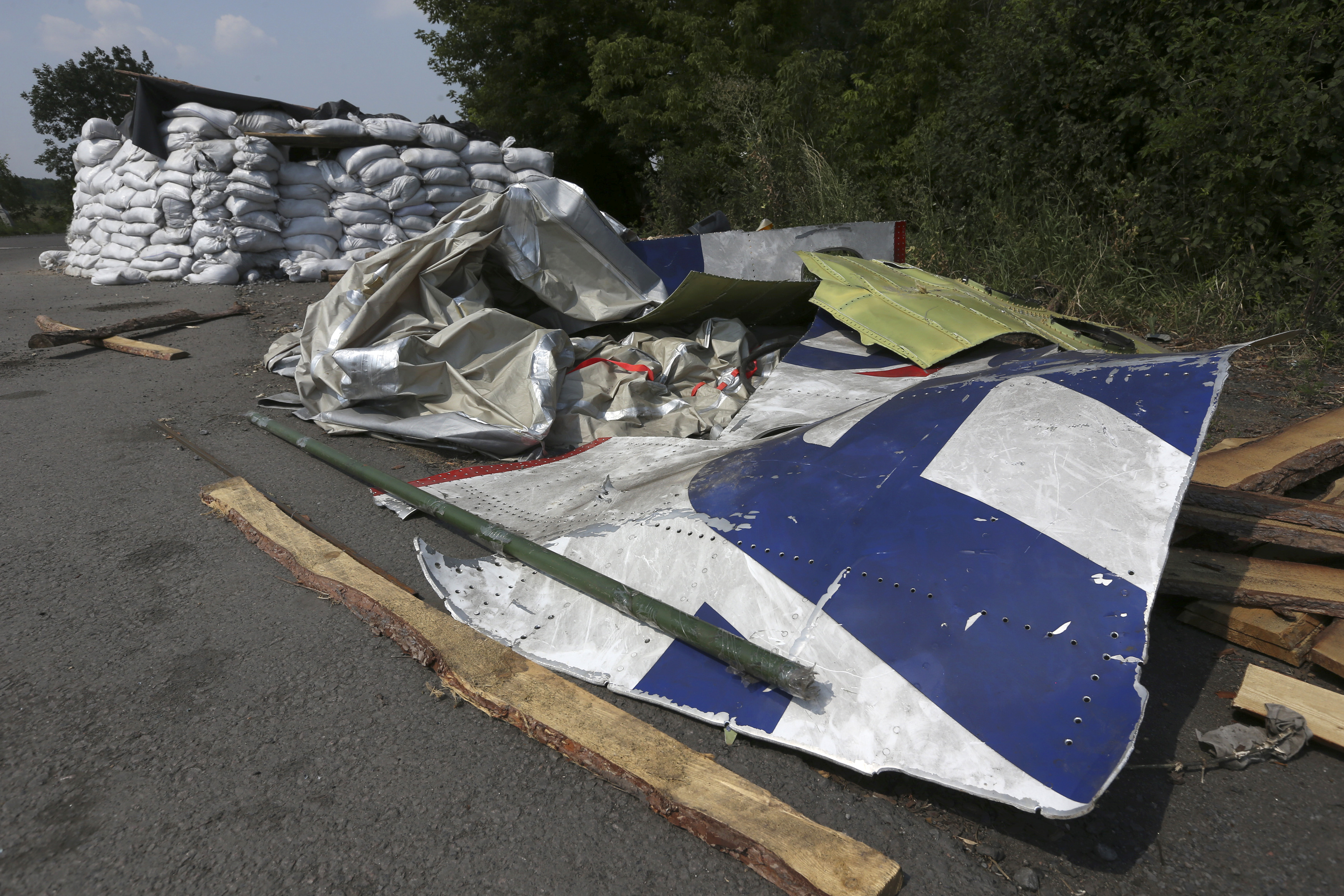 Wreckage lies near a pro-Russian separatist checkpoint at the site of the downed Malaysian airliner MH17 near the village of Rozsypne in the Donetsk region August 4, 2014.