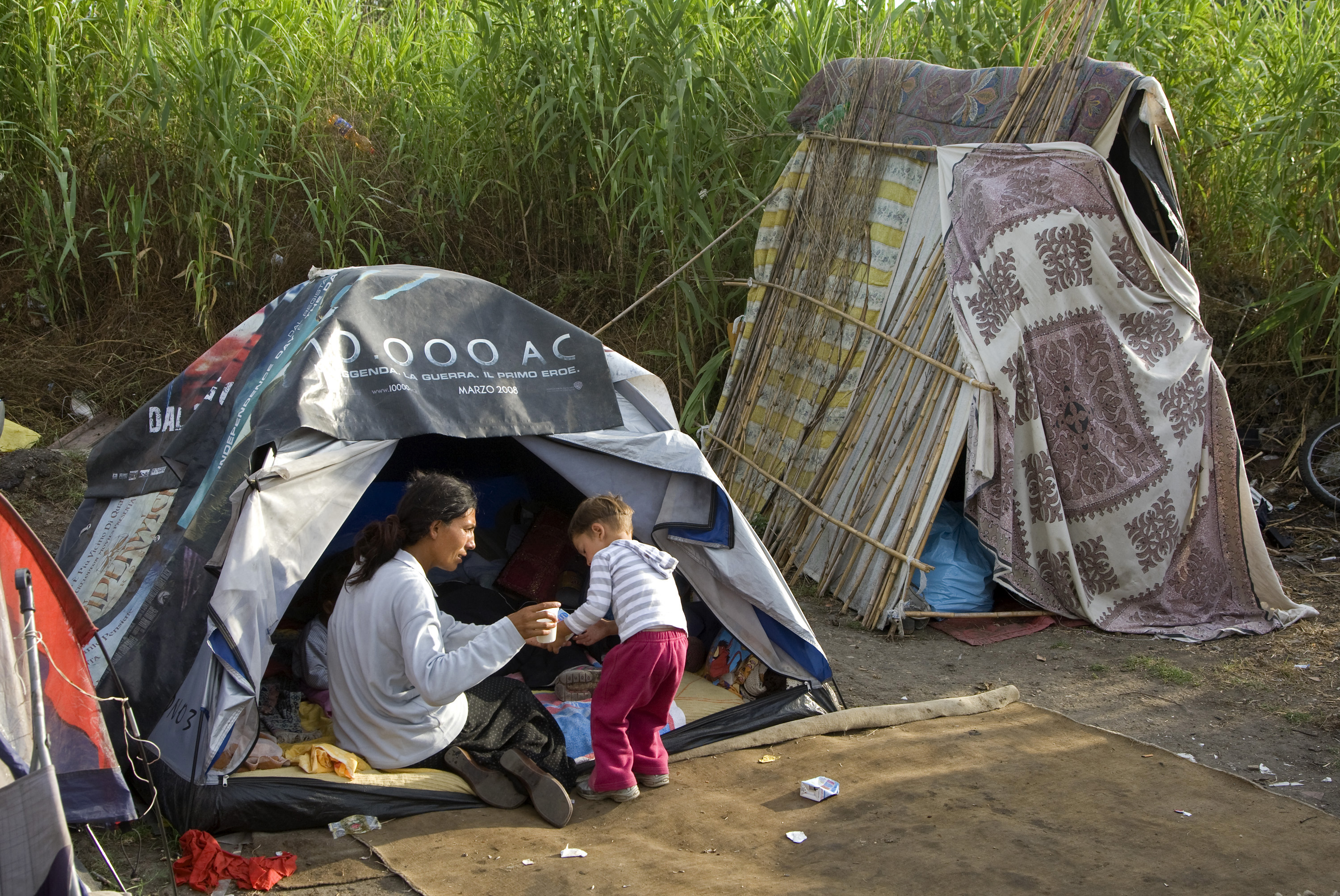 FILE - A Roma woman sits next to her tent in a camp on the outskirts of Rome, July 21, 2008.