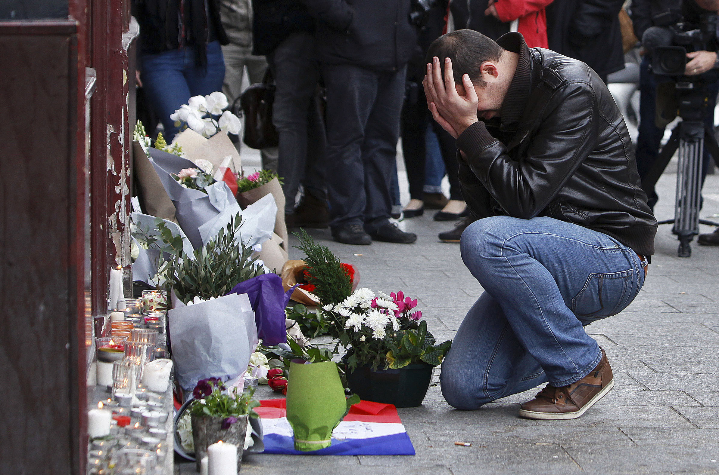 A man holds his head in his hands as he lays flowers in front of the Carillon cafe, in Paris, Nov.14, 2015.