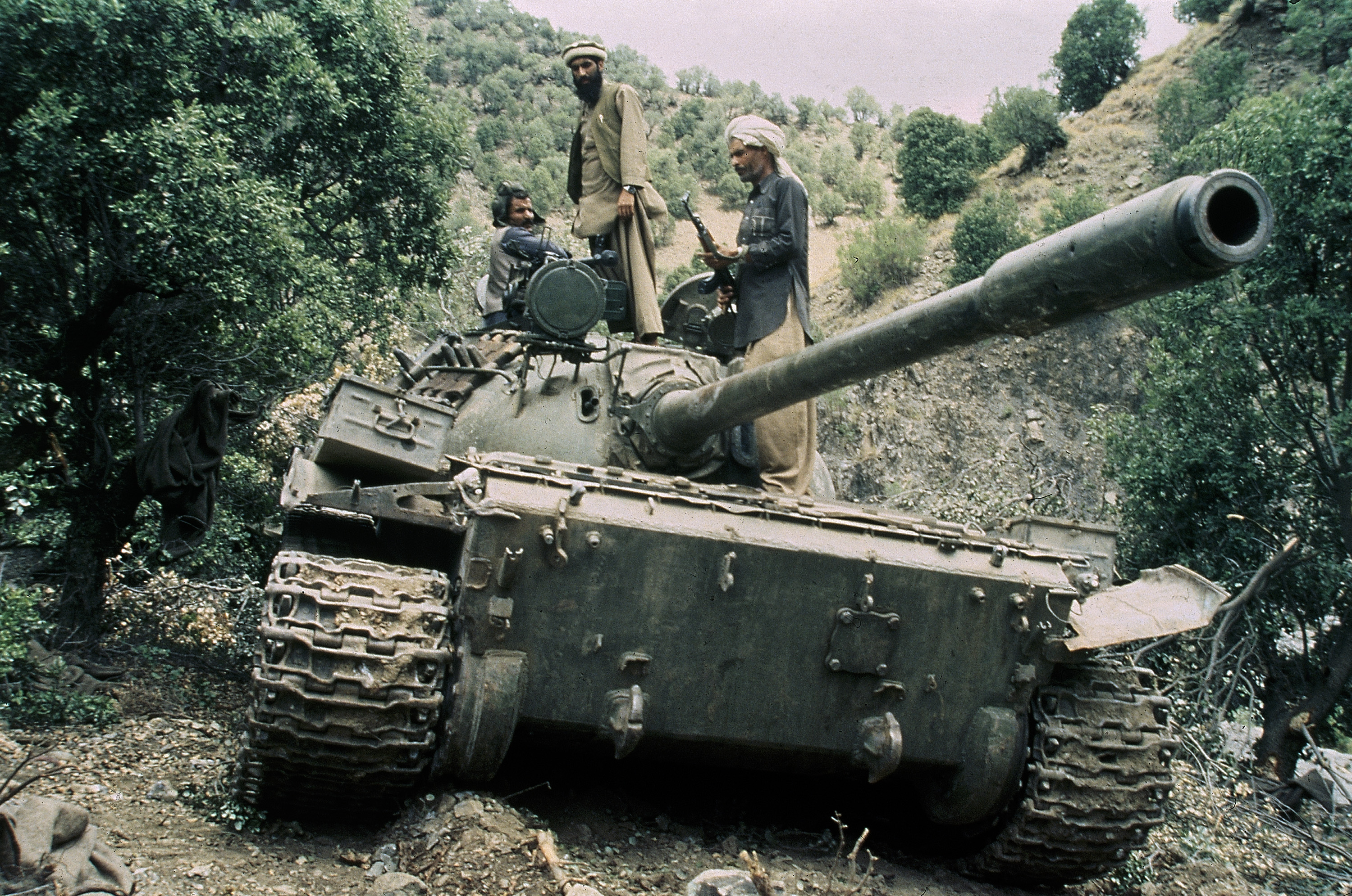 FILE - Mujahedeen guerrillas sit atop a captured Russian T-55 tank in 1987. The U.S. supported the anti-communists rebels against the Soviets.