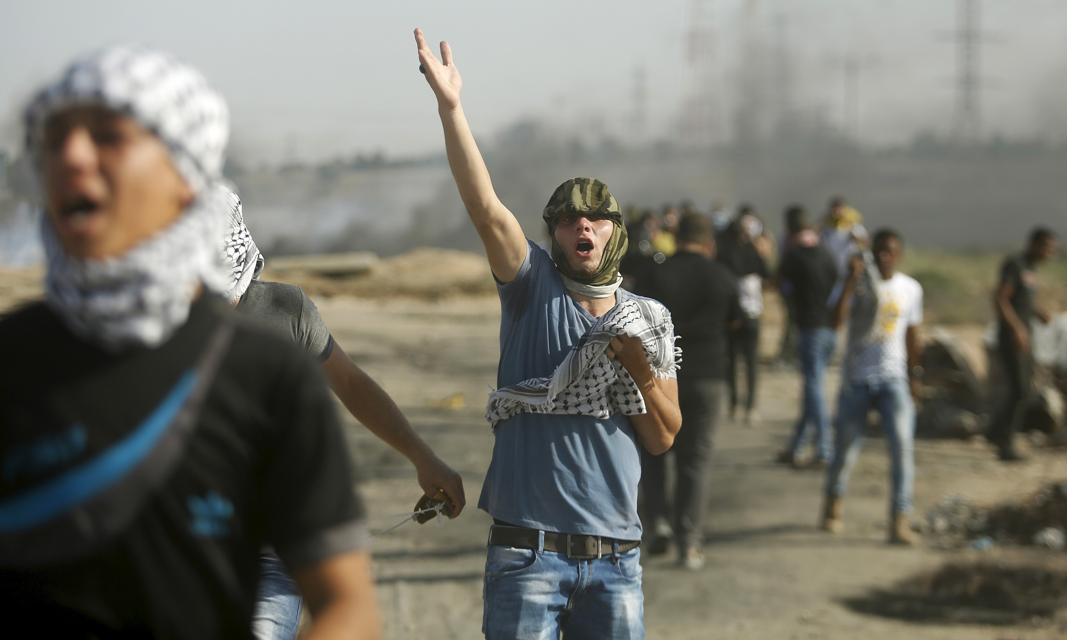 A Palestinian protester reacts to tear gas fired by Israeli troops during clashes near the border with Israel, in the east of Gaza City, Oct. 16, 2015.