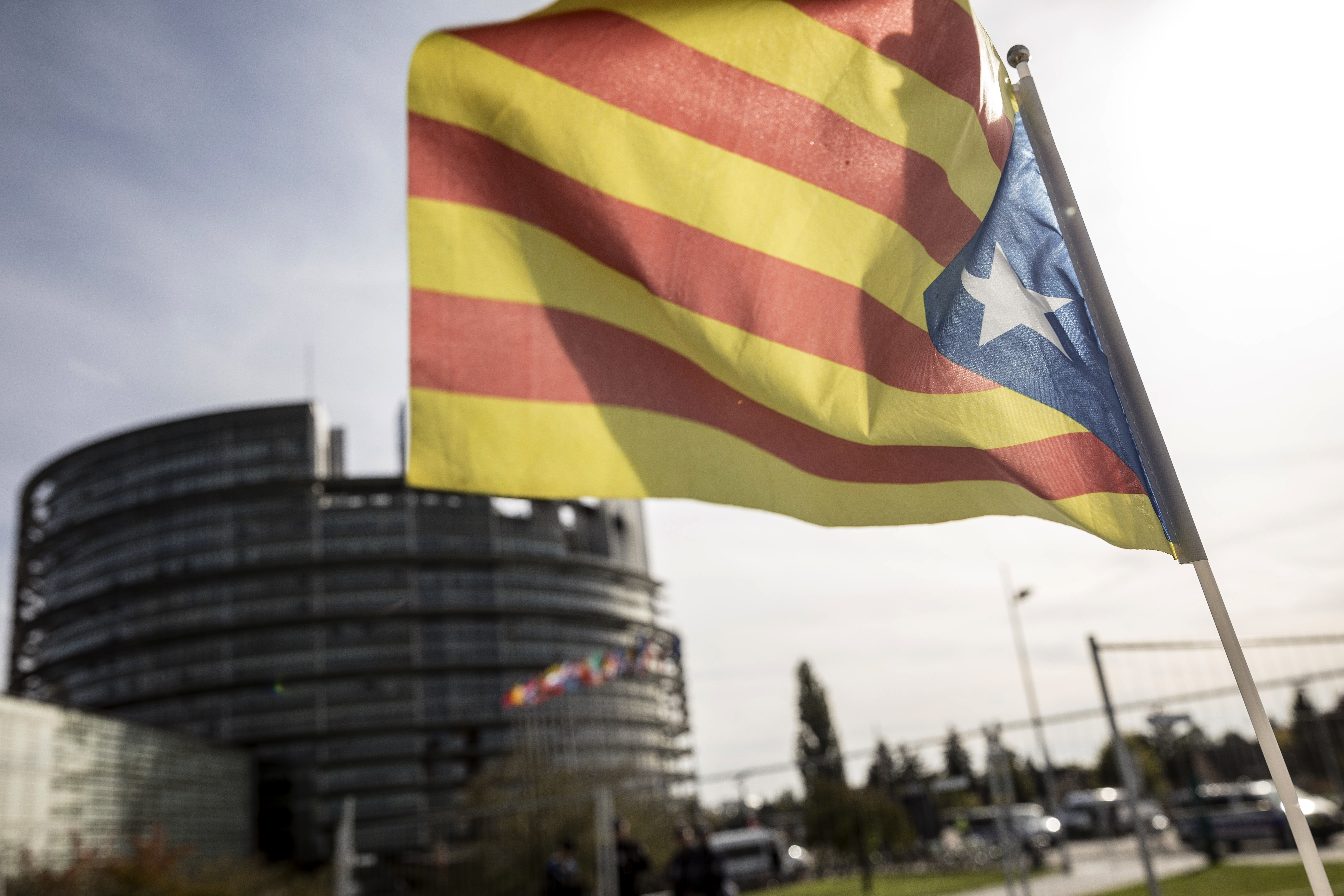 A demonstrator waves a Catalan flag in support of the disputed independence vote Sunday in Catalonia during a protest in front of the European Parliament in Strasbourg, France, Oct. 4, 2017.