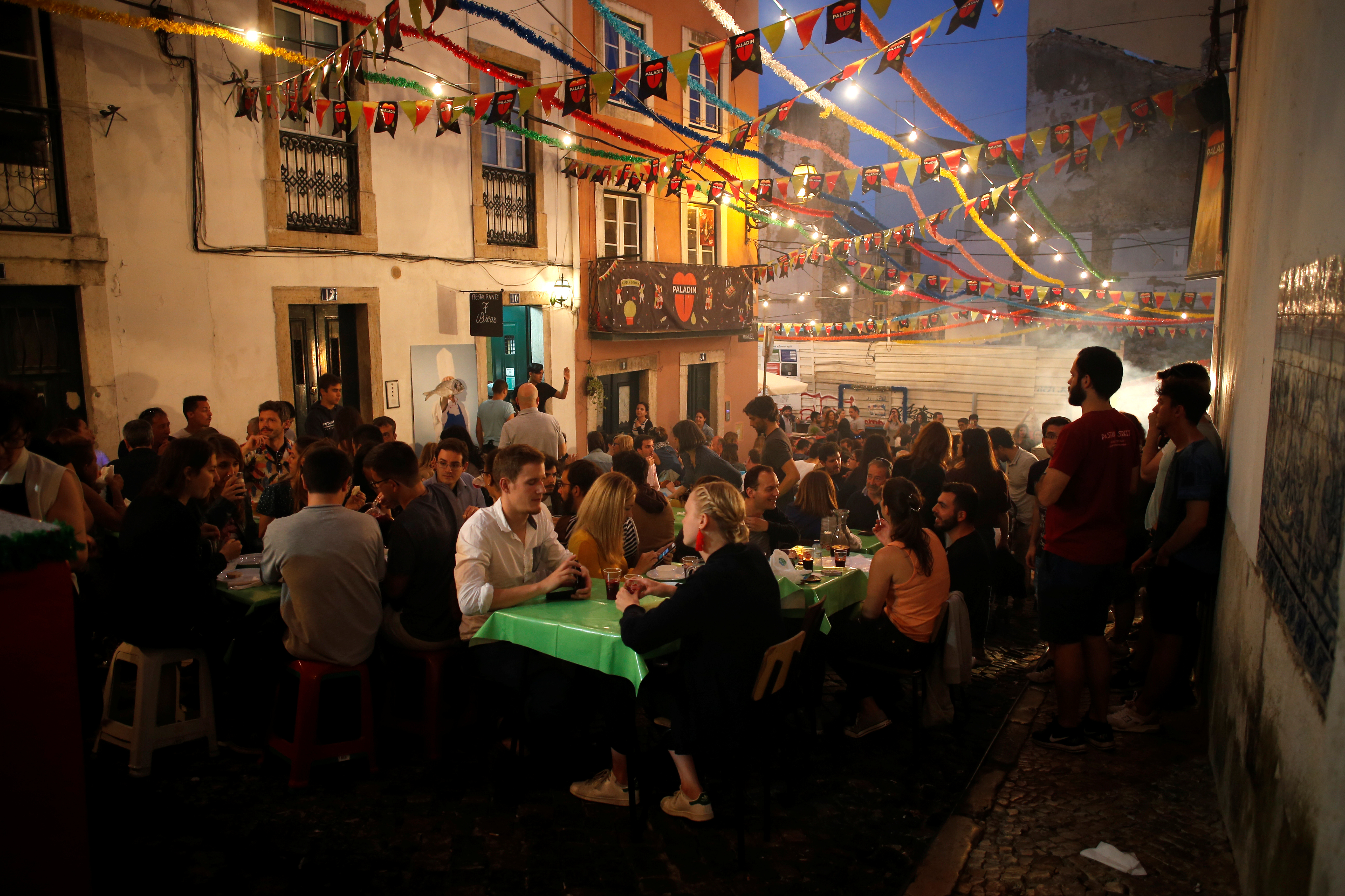 People sit outside in the Alfama neighborhood during the Festival of Popular Saints in Lisbon, Portugal, June 16, 2018.