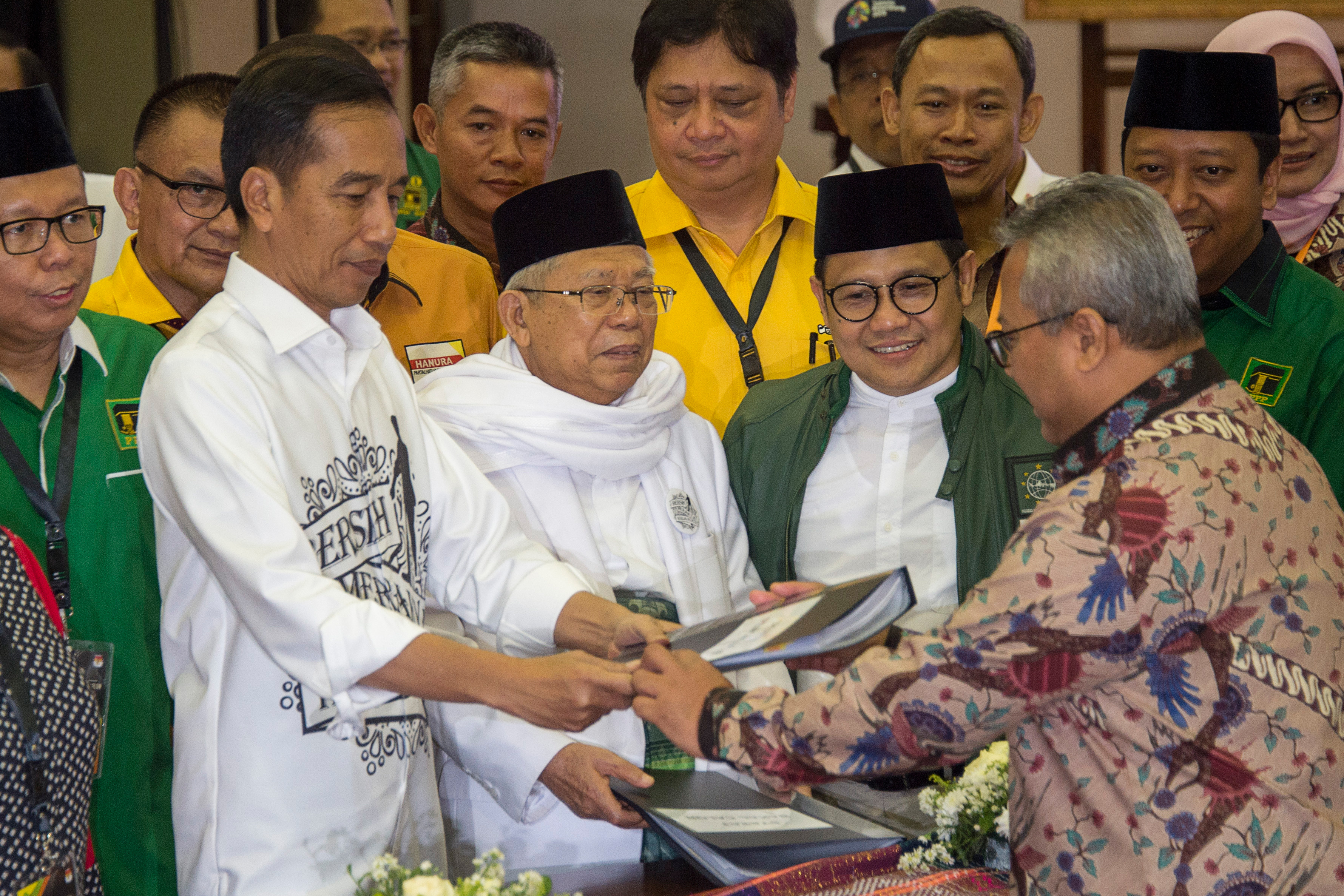 Indonesia's President Joko Widodo, front left, and the head of Indonesian Ulema Council Maruf Amin, center, submit their documents to election commission officials in Jakarta, Aug. 10, 2018, during their registration for the 2019 presidential electio...