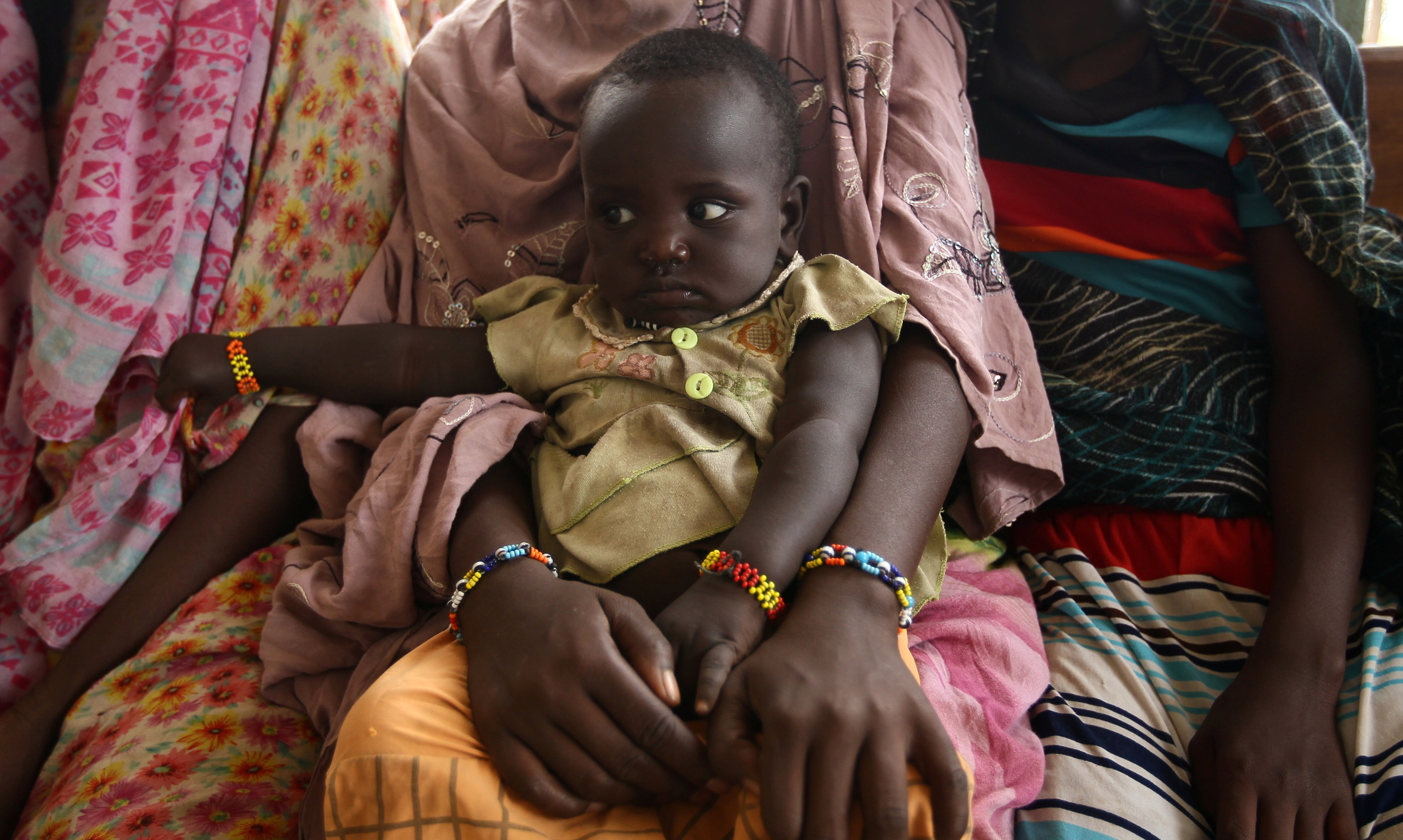 A woman holds her child as they wait to receive treatment in Kobo health center in Kobo village, one of the drought stricken areas of Oromia region, in Ethiopia, April 28, 2016.