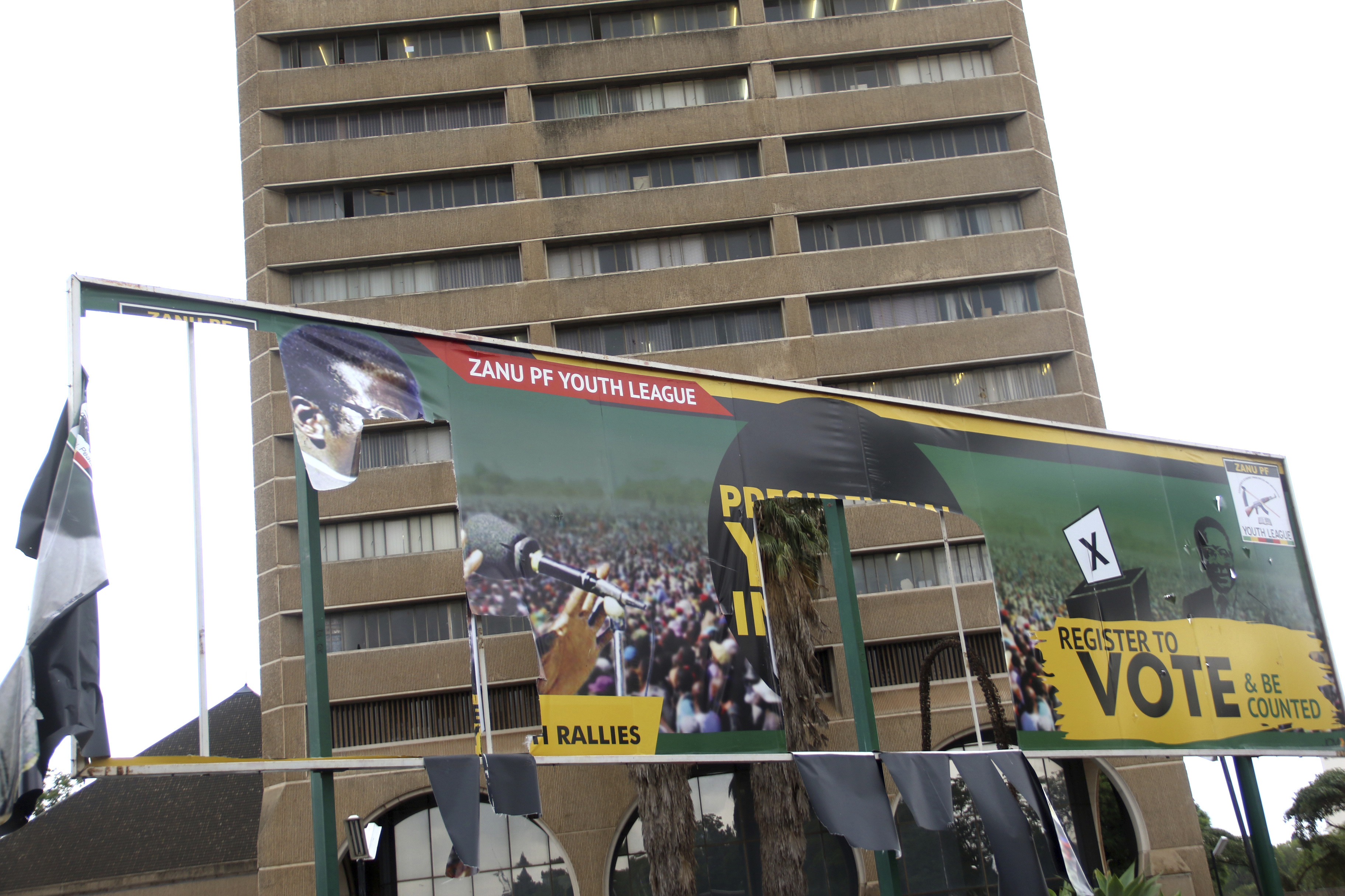 FILE - An old ripped election banner bearing a portrait of ousted President Robert Mugabe outside the headquarters of the ruling ZANU PF building in Harare, Nov. 19, 2017.