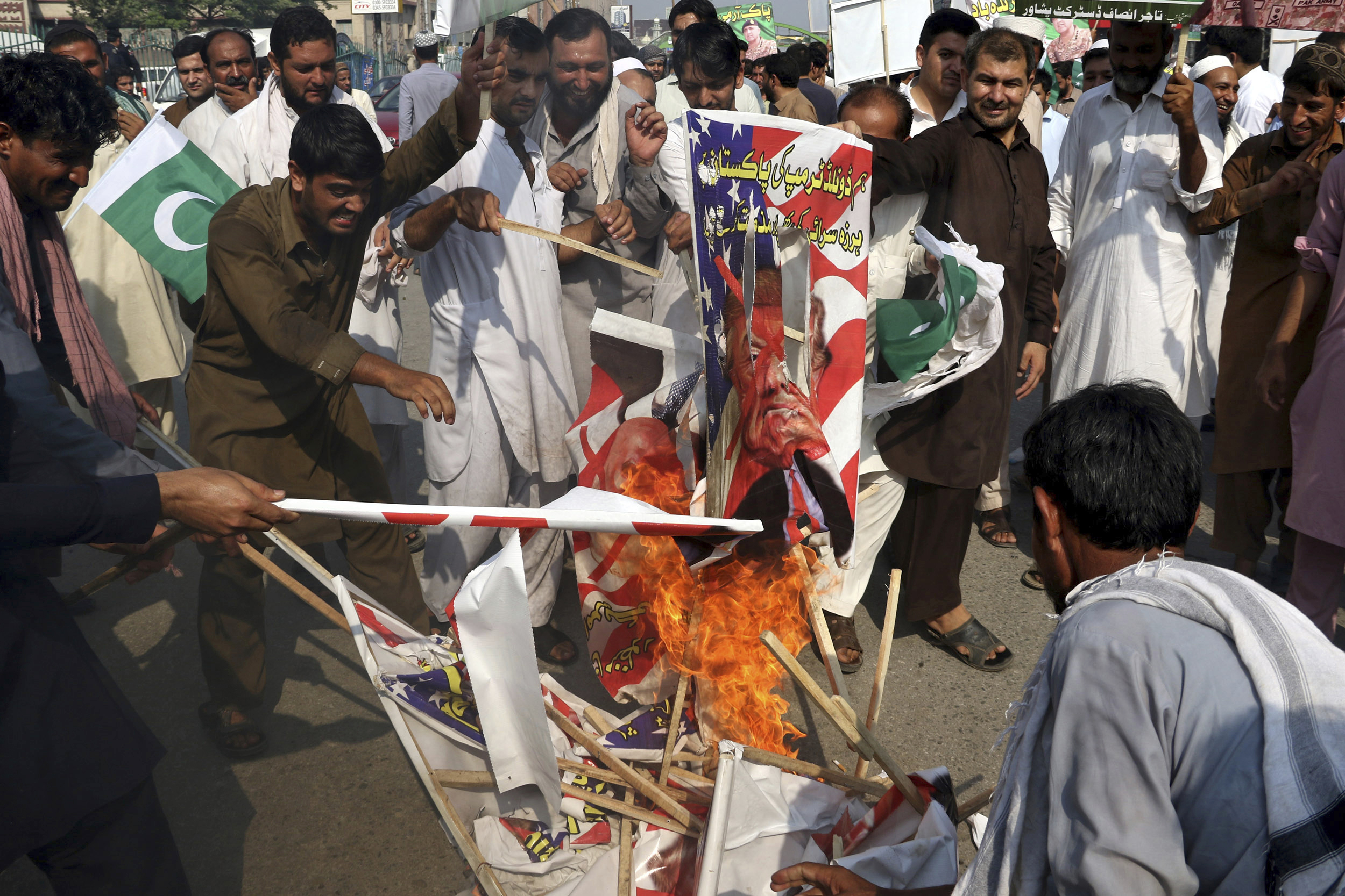 Pakistani protesters burn posters of U. S. President Donald Trump in Peshawar, Pakistan, Aug. 30, 2017. Protesters have objected to Trump's allegation that Islamabad is harboring militants who battle U.S. forces in Afghanistan.