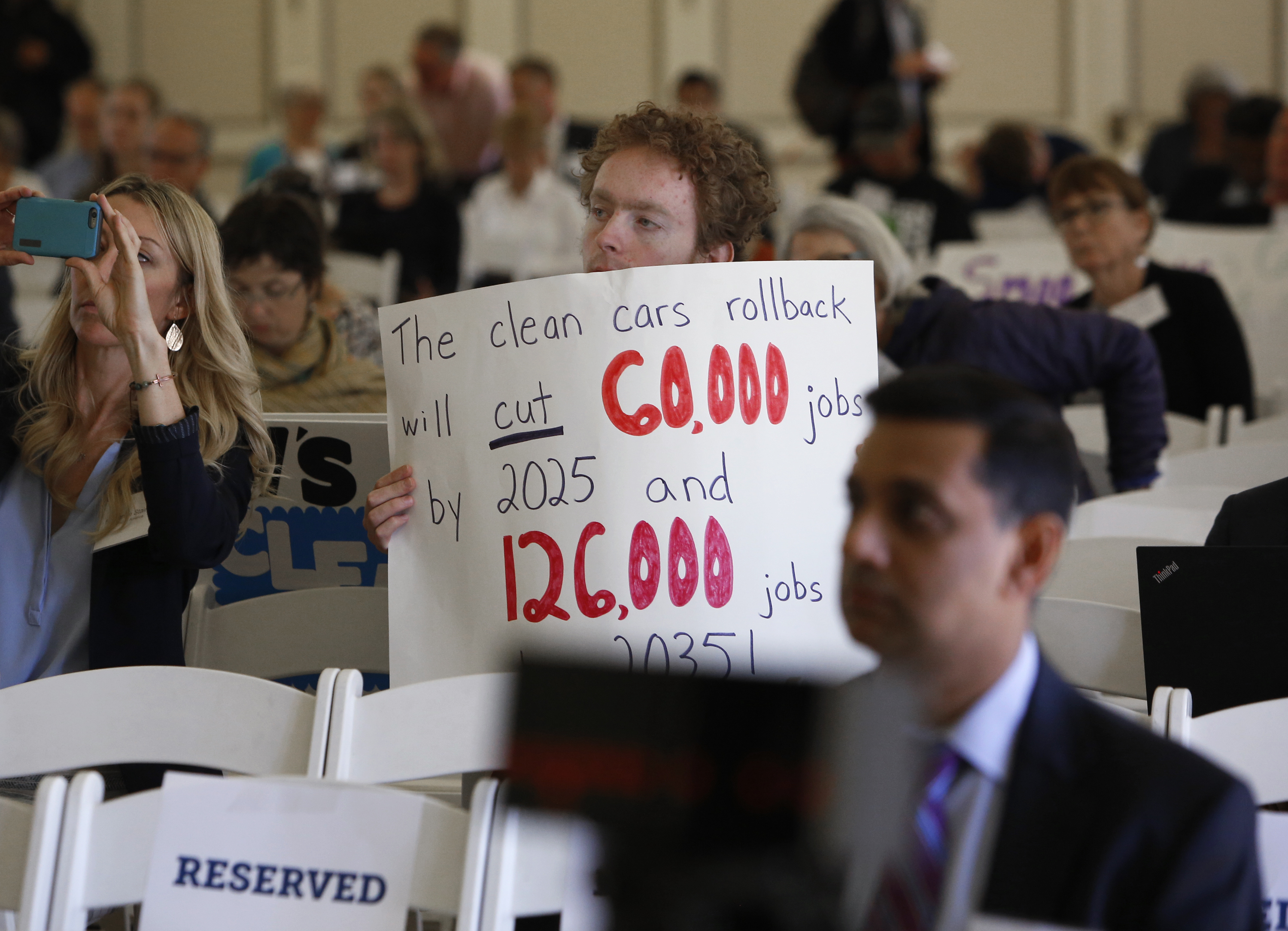 FILE - Benjamin Tuggy holds a sign while listening to speakers during the first of three public hearings on the Trump administration's proposal to roll back car-mileage standards in a region with some of the nation's worst air pollution in Fresno, Ca...