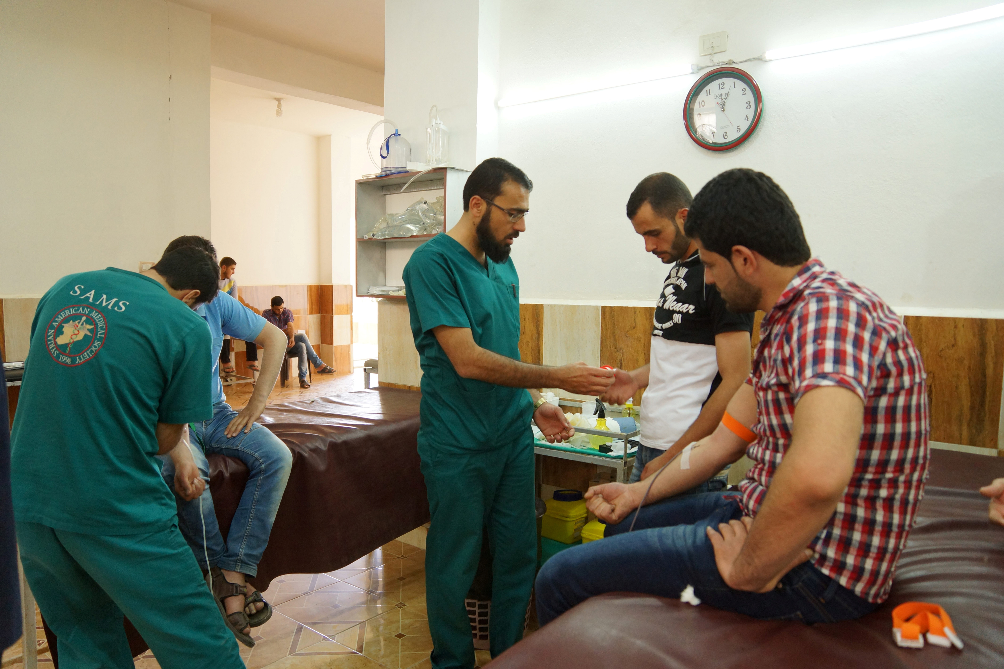 Medics help men donating blood during a campaign to supply blood to a hospital in the rebel-held town of Dael, in Deraa Governorate, Syria May 1, 2016.