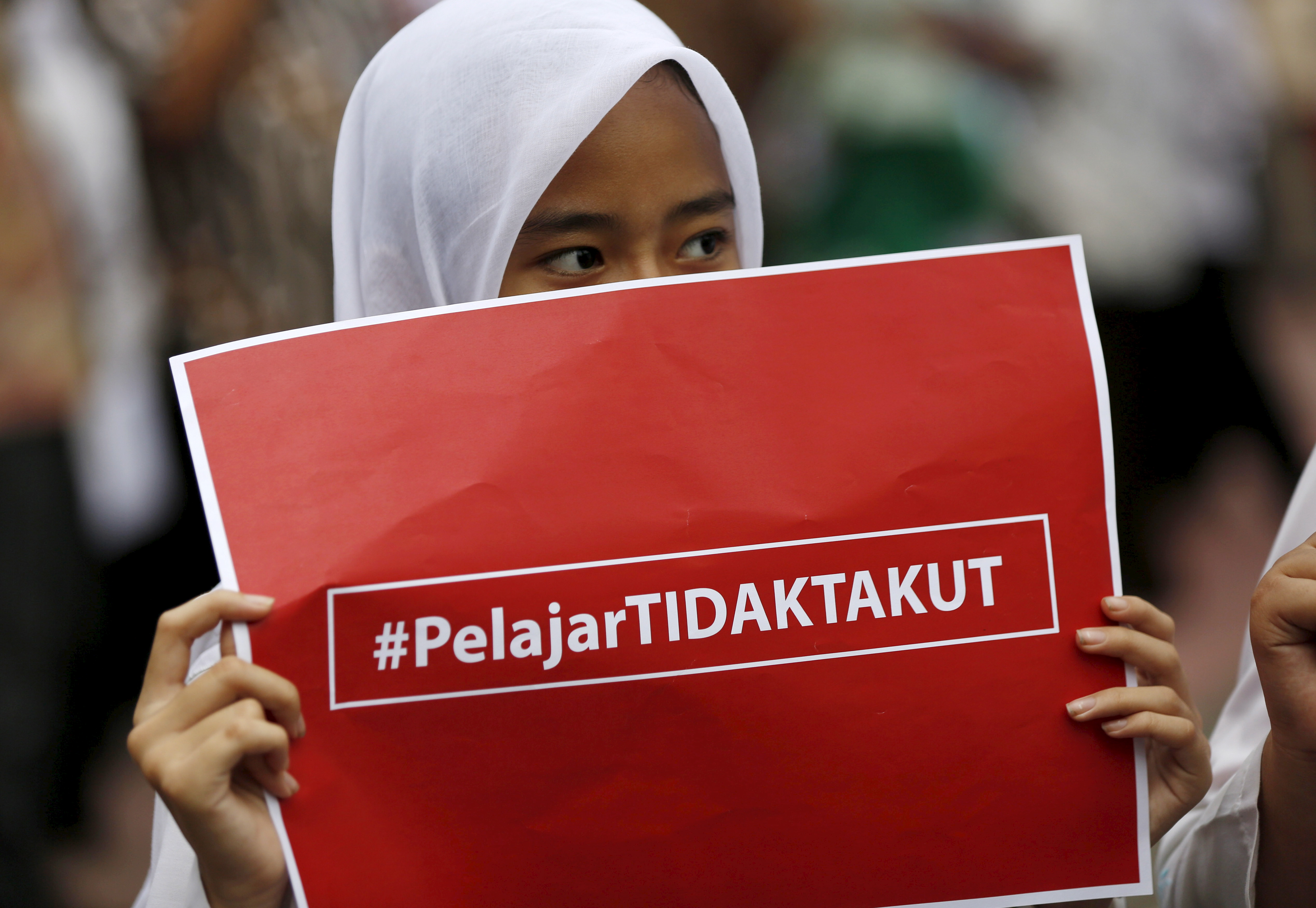 """An elementary school student holds a placard reading """"Students are not afraid"""" at a small anti-terrorism rally in central Jakarta a day after a gun and bomb attack in the city, Jan. 15, 2016."""