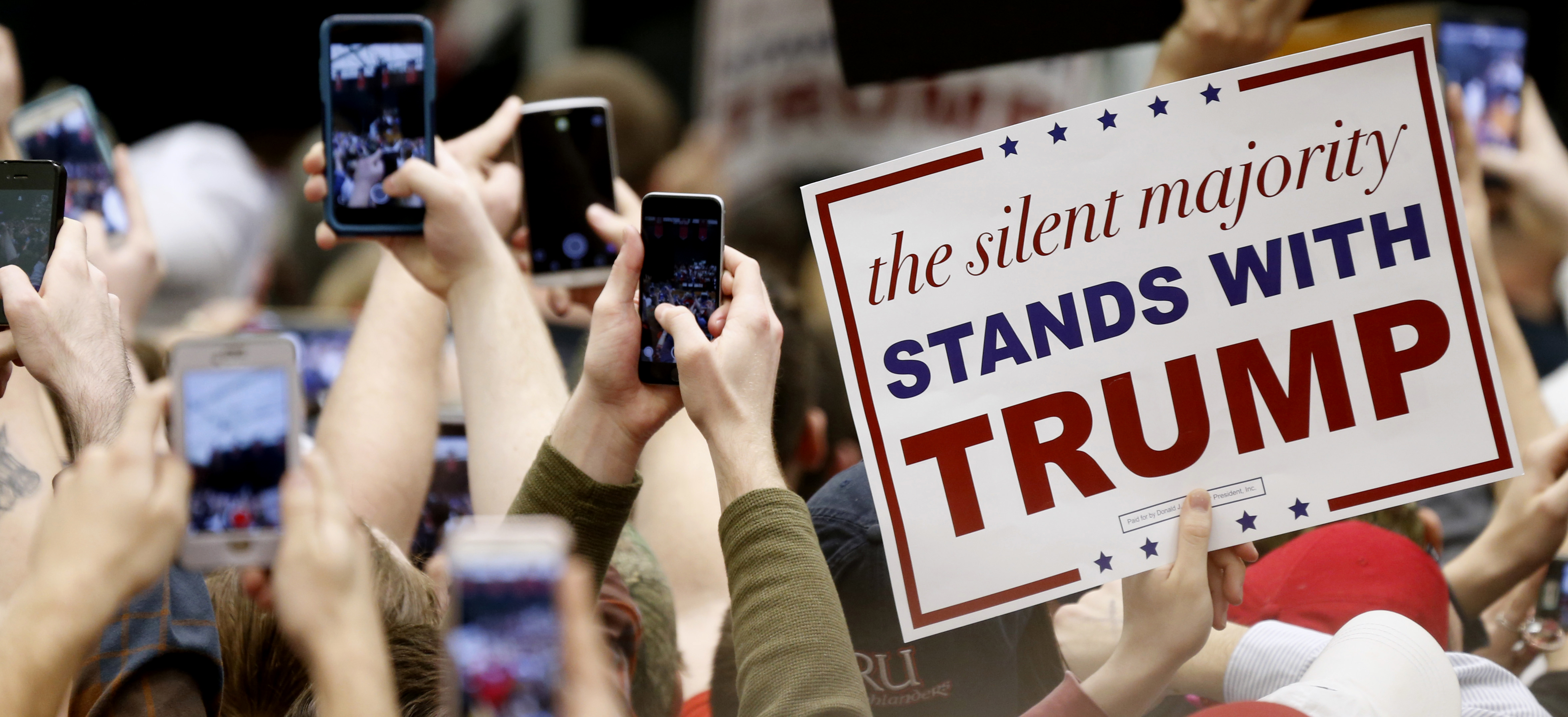 Supporters of Republican presidential candidate, Donald Trump hold up phones and signs as the arrives for a rally at Radford University in Radford, Virginia, Feb. 29, 2016.