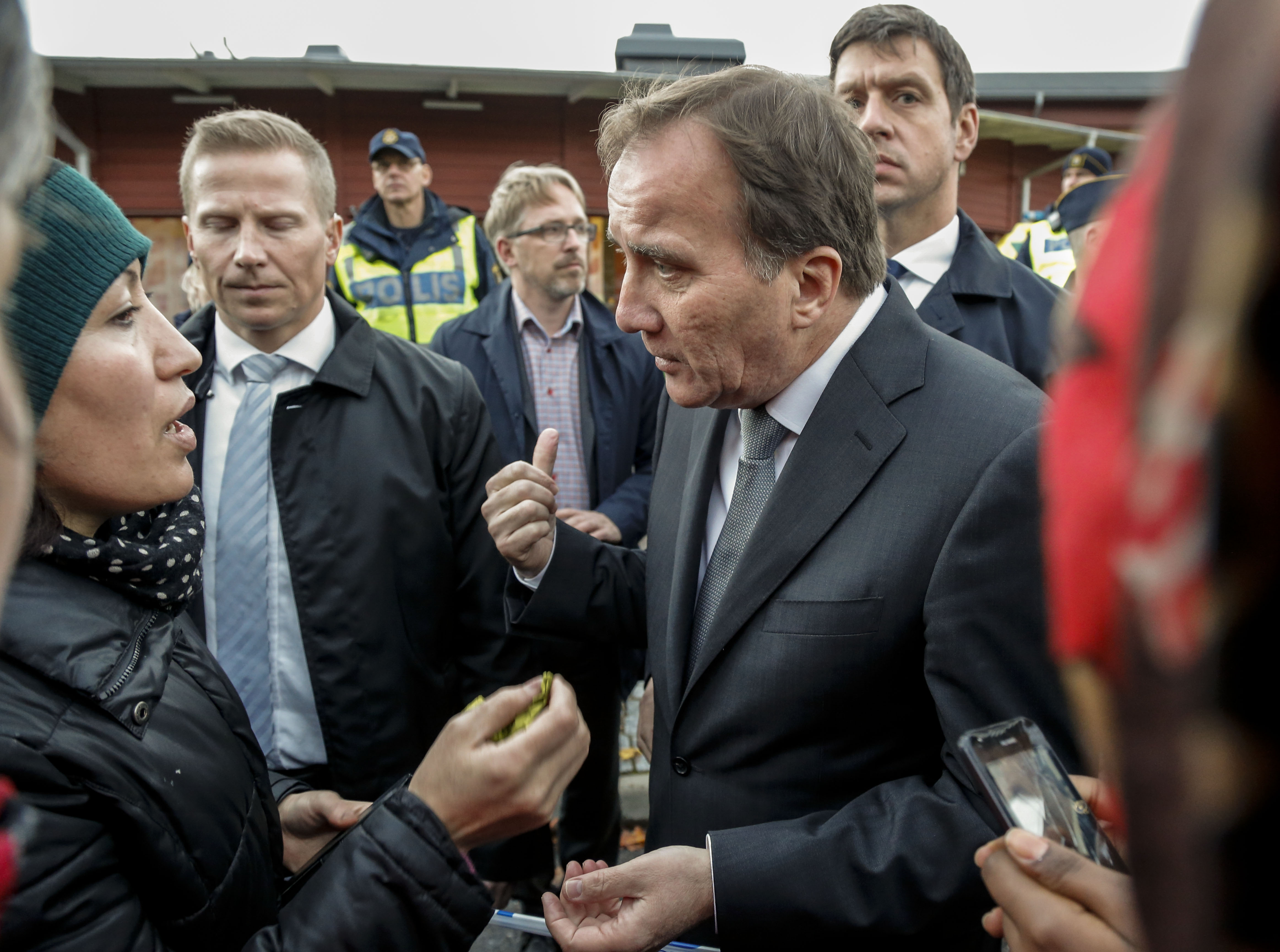 Prime Minister Stefan Lofven, right, talks to local people near the school Thursday afternoon where a masked man wielding what looked like a sword stabbed four people Thursday Oct. 22, 2015, in Trollhattan, Southern Sweden.