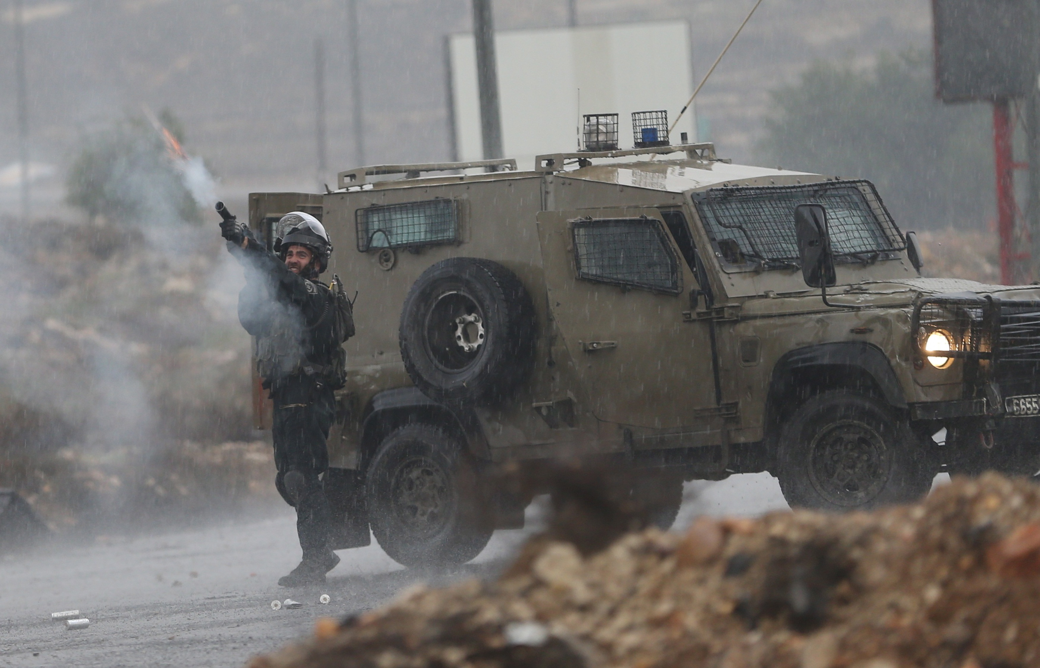 An Israeli border police officer fires tear a gas canister during clashes with Palestinian protesters near the Jewish settlement of Bet El, near the West Bank city of Ramallah, Nov. 5, 2015.