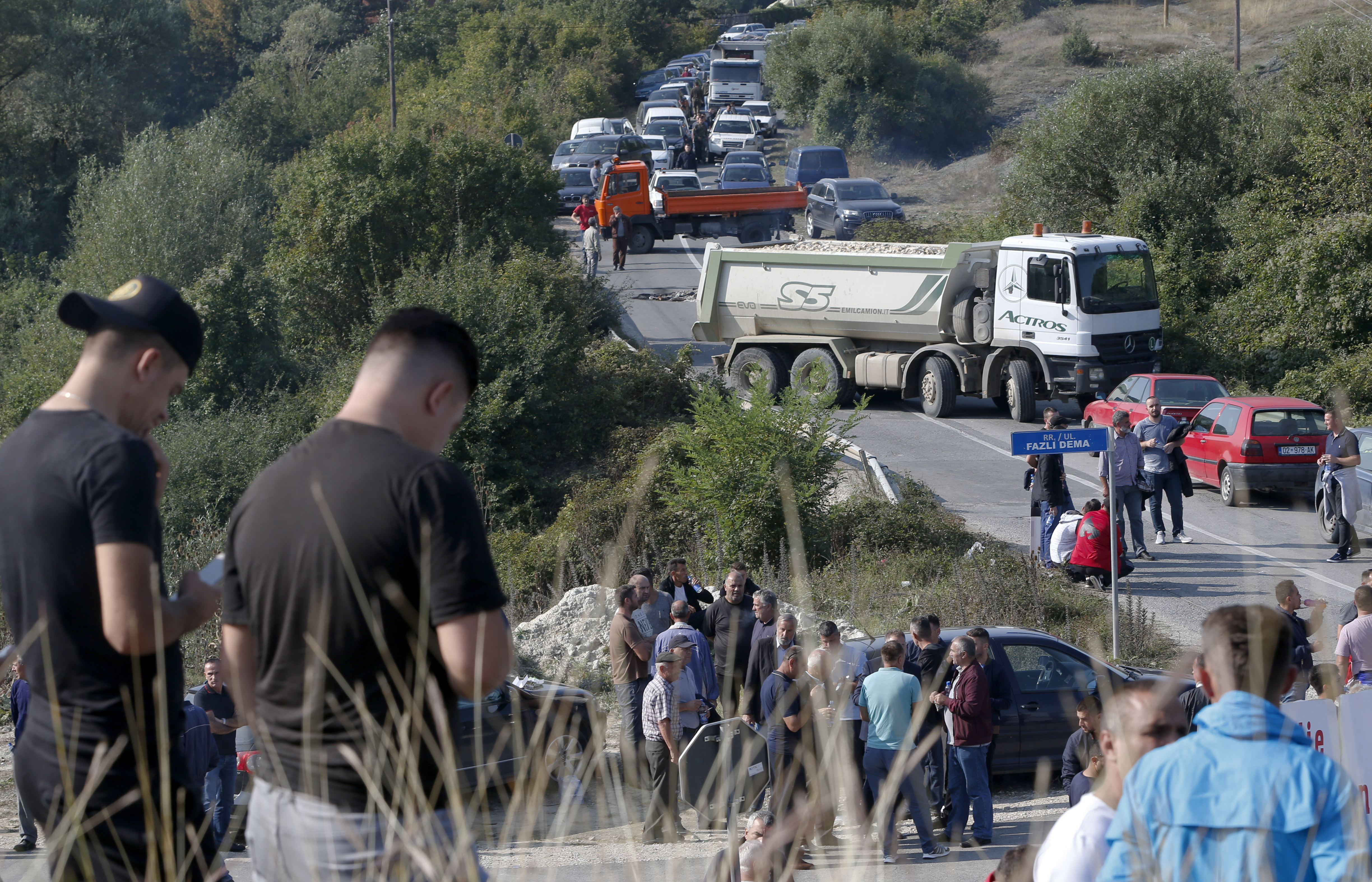 Trucks are parked on the road at a roadblock in Vojtesh, Kosovo, Sept. 9, 2018.