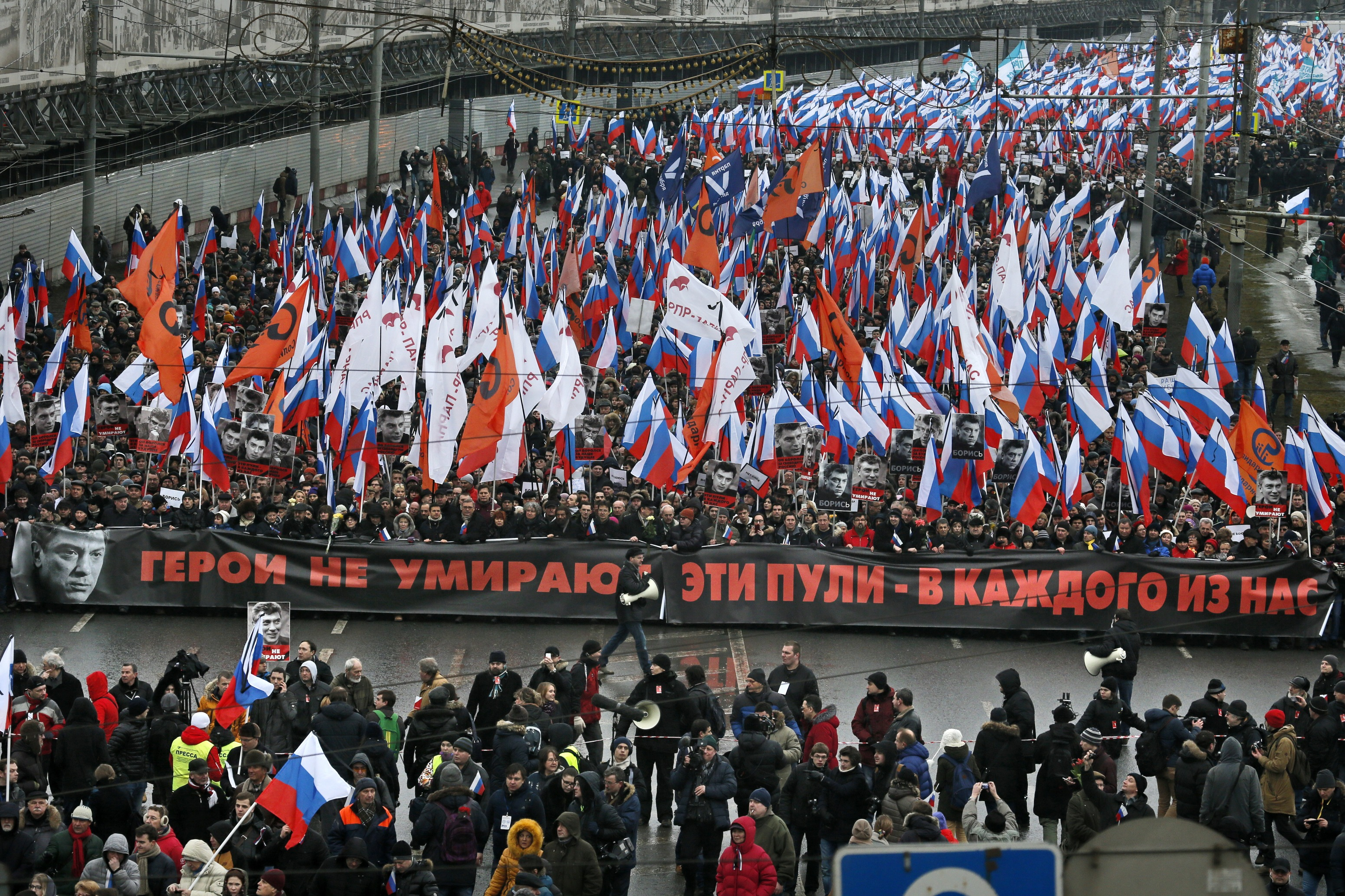 """People carry a huge banner reading """"Those bullets for everyone of us, heroes never die!"""" as they march in memory of opposition leader Boris Nemtsov who was gunned down on Friday near the Kremlin, in Moscow, Russia, March 1, 2015."""