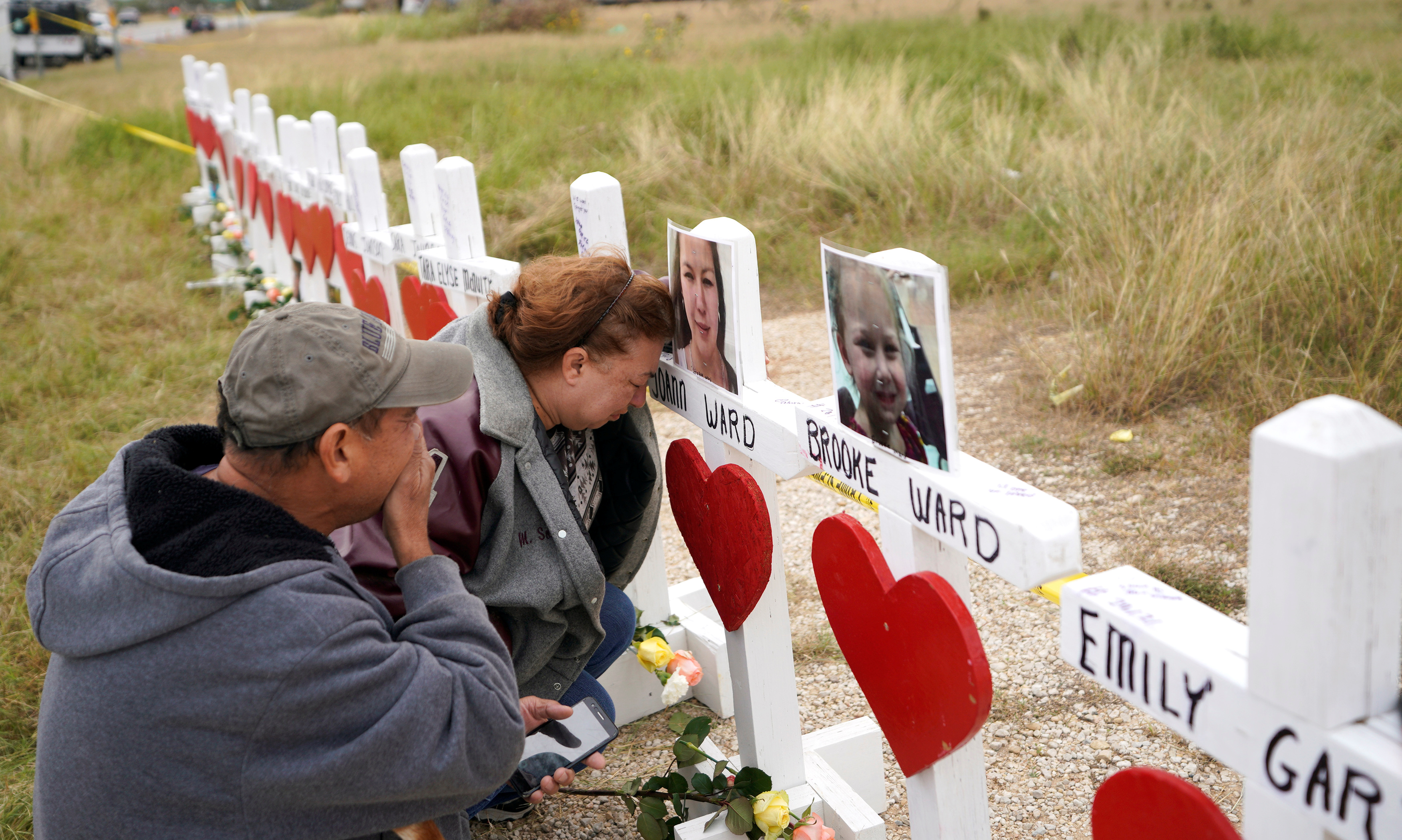 Lorenzo Flores (L) and Terrie Smith react at a line of crosses in remembrance of those killed in the shooting at the First Baptist Church of Sutherland Springs, Texas, U.S., November 9, 2017.